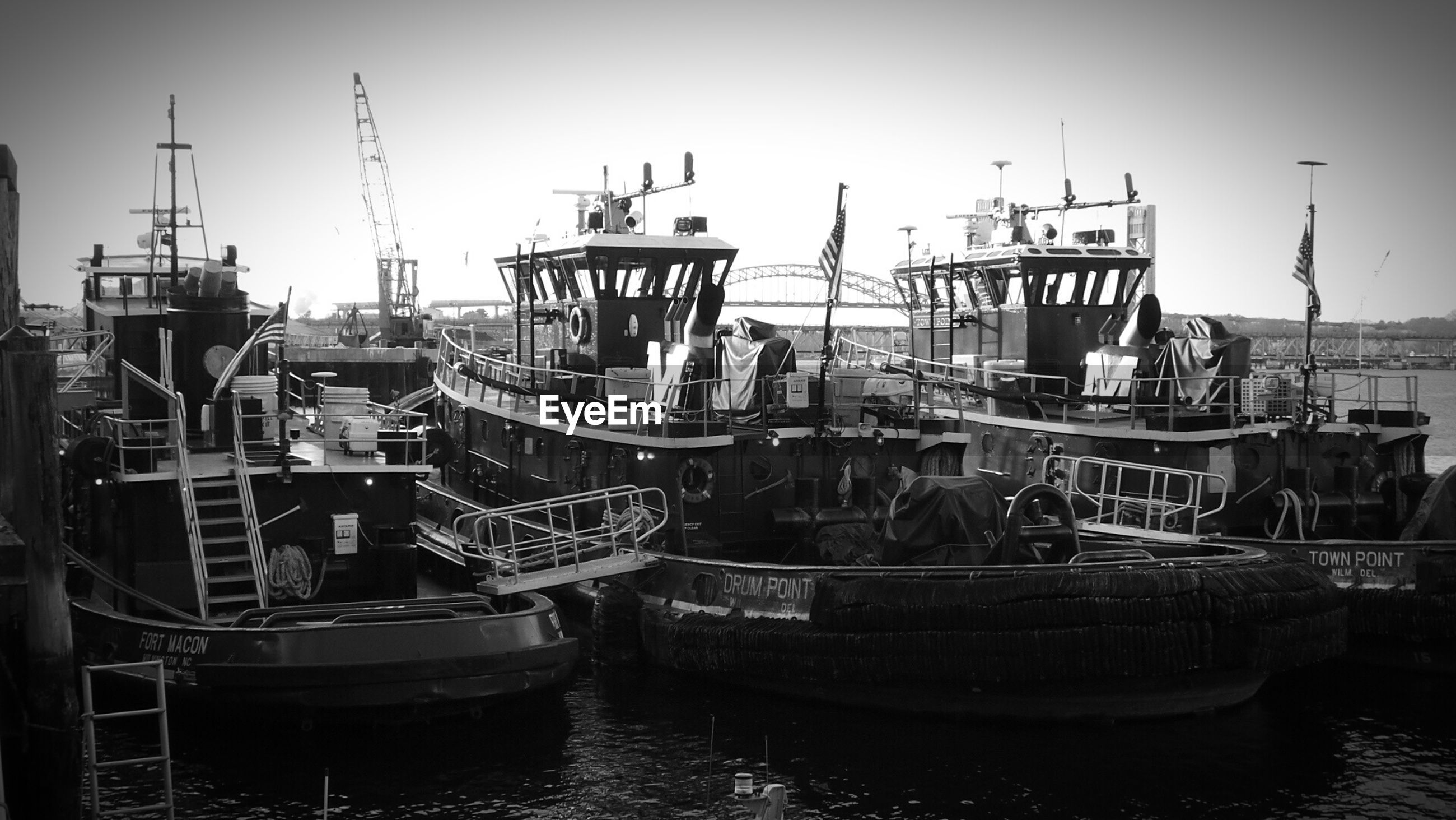 Tugboats at harbor against sky