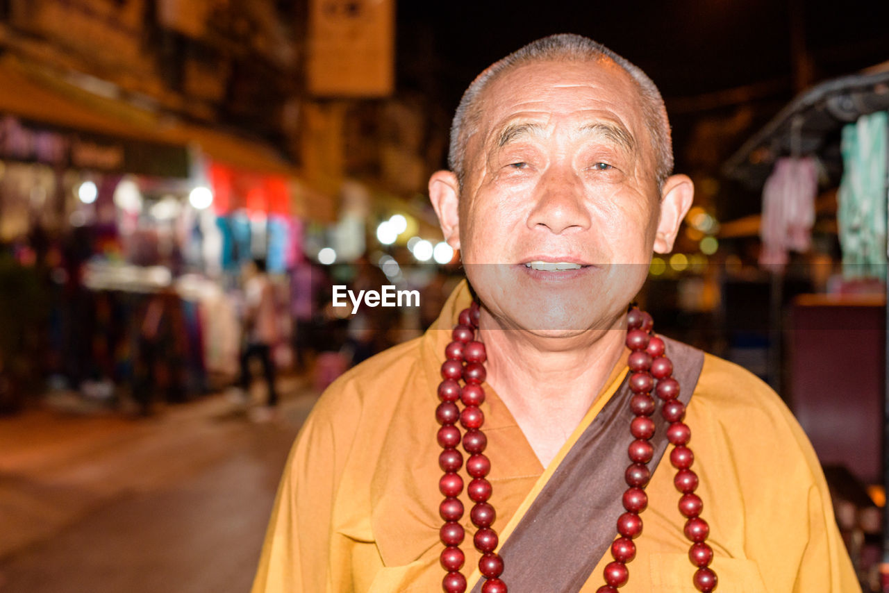 real people, one person, focus on foreground, portrait, necklace, headshot, looking at camera, front view, smiling, retail, men, lifestyles, outdoors, cheerful, night, happiness, close-up, people