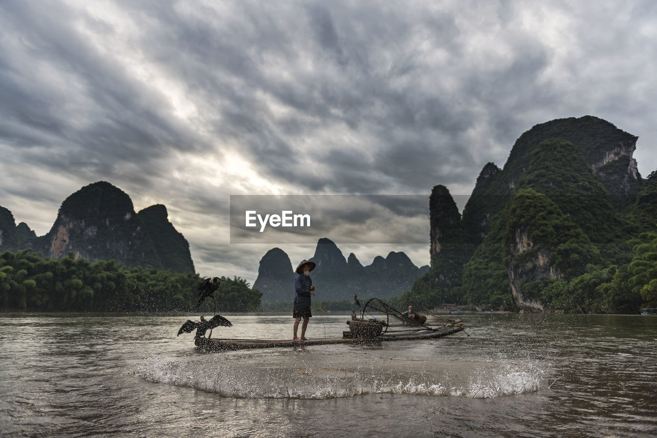 mountain, rock - object, nature, sky, sea, water, full length, outdoors, one person, beauty in nature, scenics, cloud - sky, tranquility, men, real people, tranquil scene, women, day, longtail boat, standing, ankle deep in water, nautical vessel, adult, mammal, adults only, people