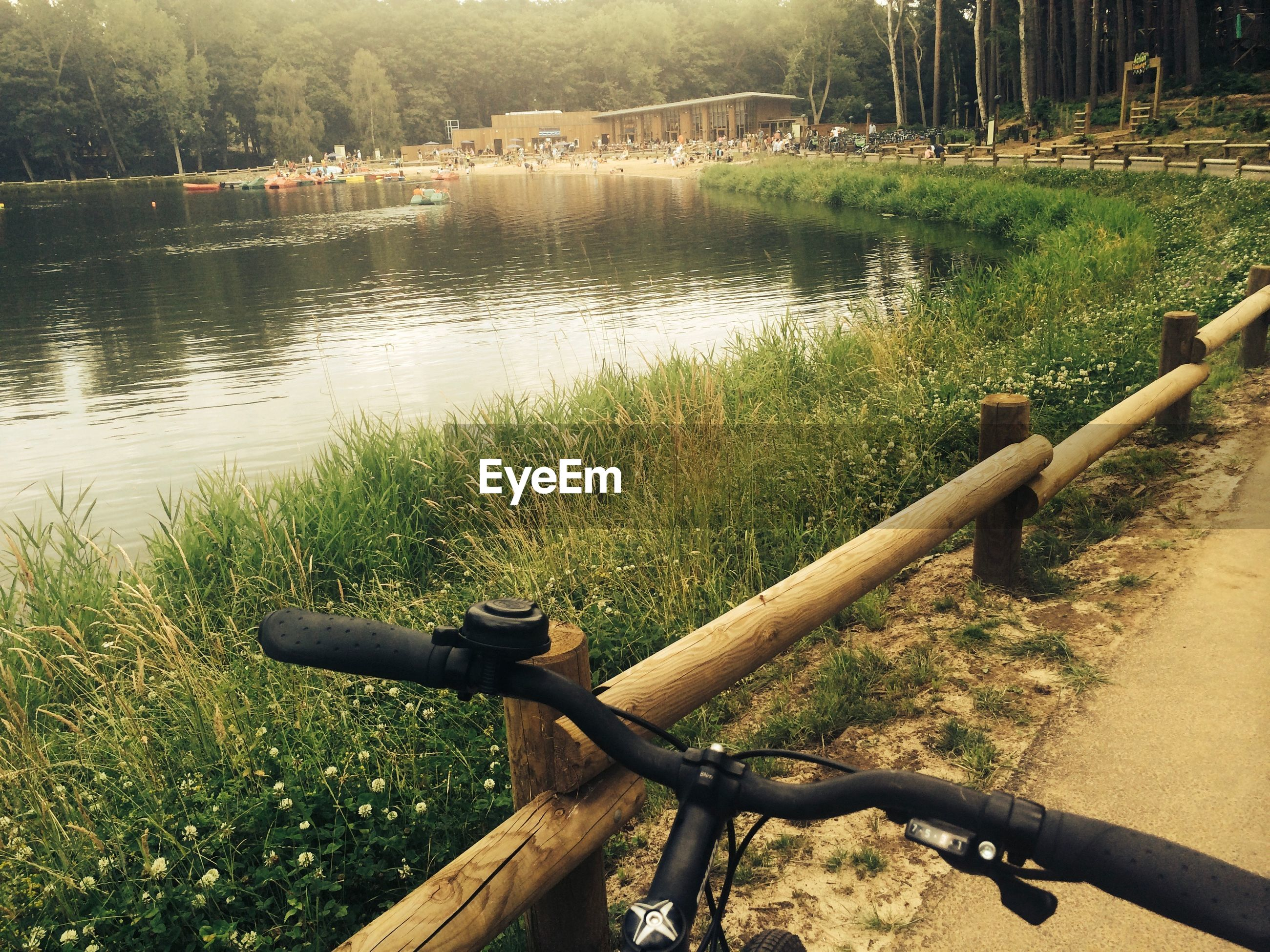 Cropped image of bicycle on road by lake