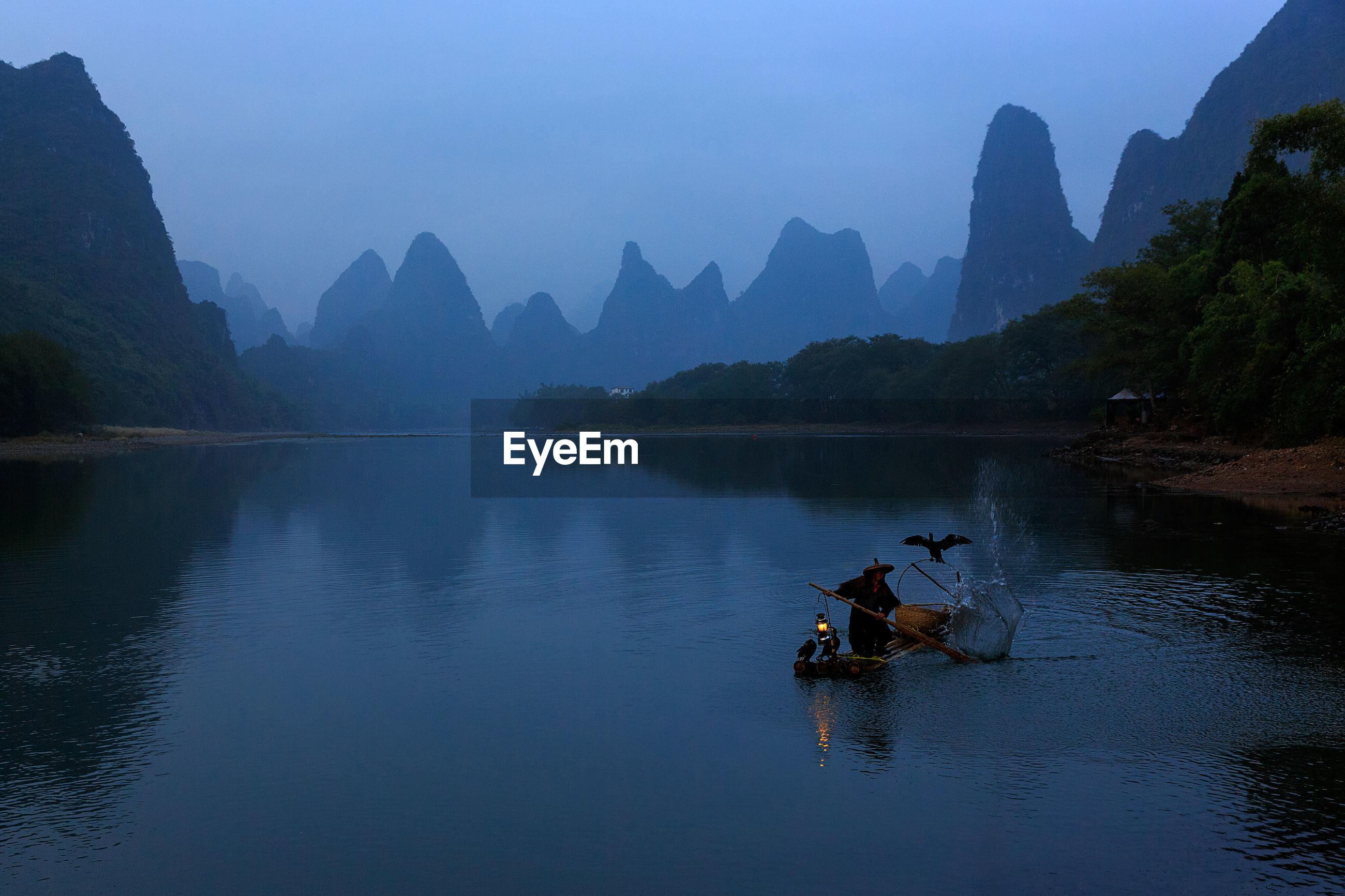 Fisherman in boat on river at morning