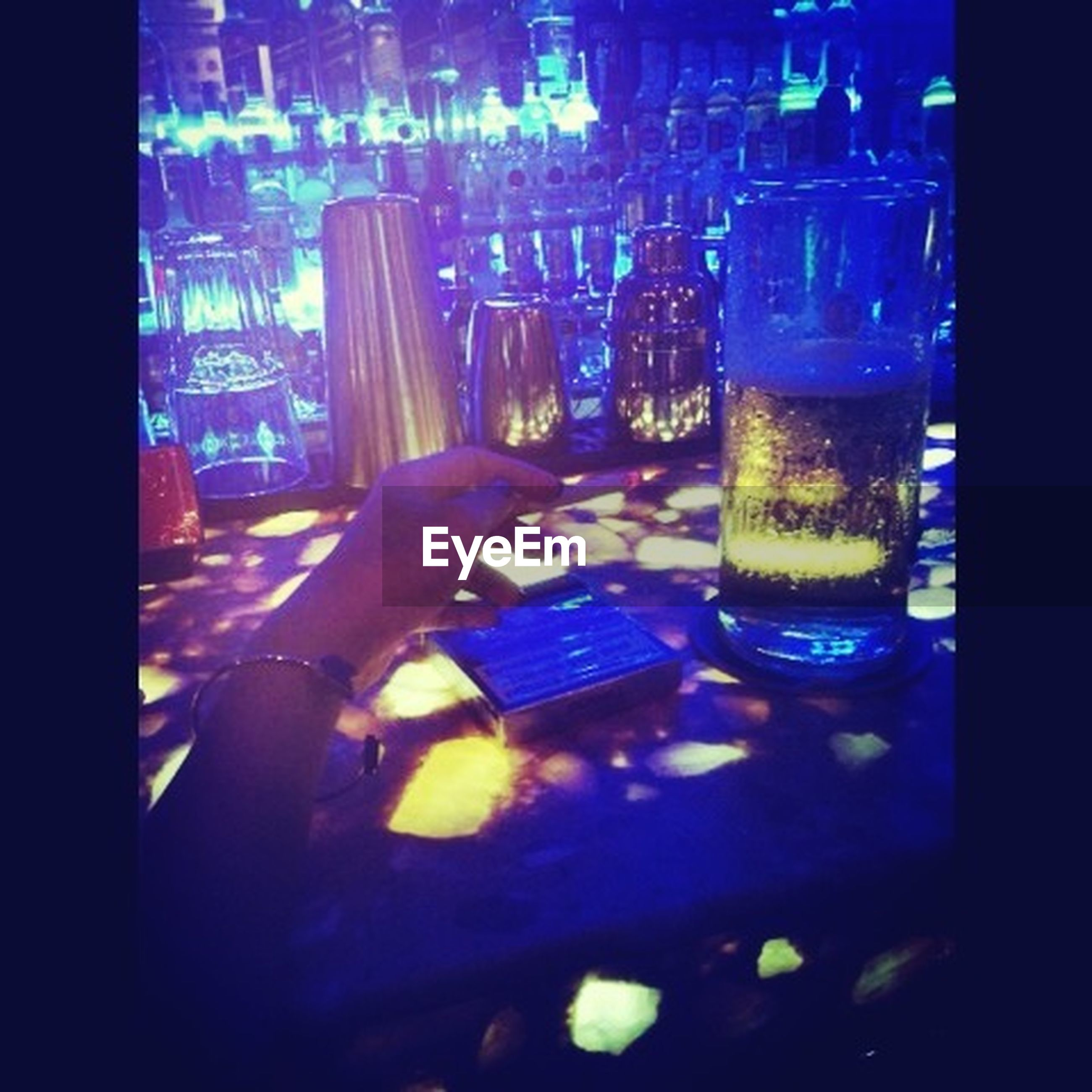 indoors, glass - material, illuminated, person, transparent, blue, close-up, auto post production filter, technology, window, transfer print, men, food and drink, reflection, holding, part of, night, bottle