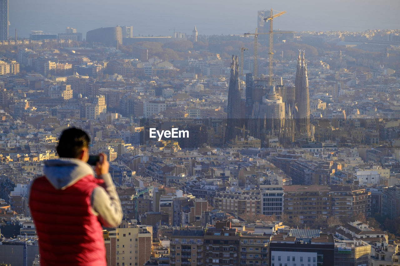 Rear View Of Man Photographing Sagrada Familia Amidst City