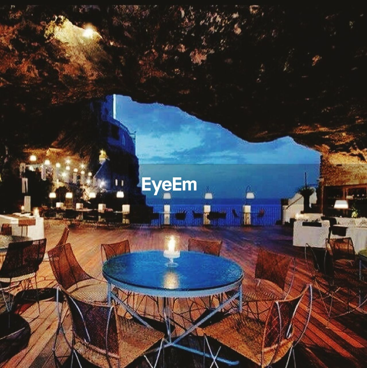 illuminated, night, table, chair, water, no people, dusk, sky, architecture, blue, tourist resort, swimming pool, outdoors, nature, building exterior, built structure, mountain, luxury hotel, sea