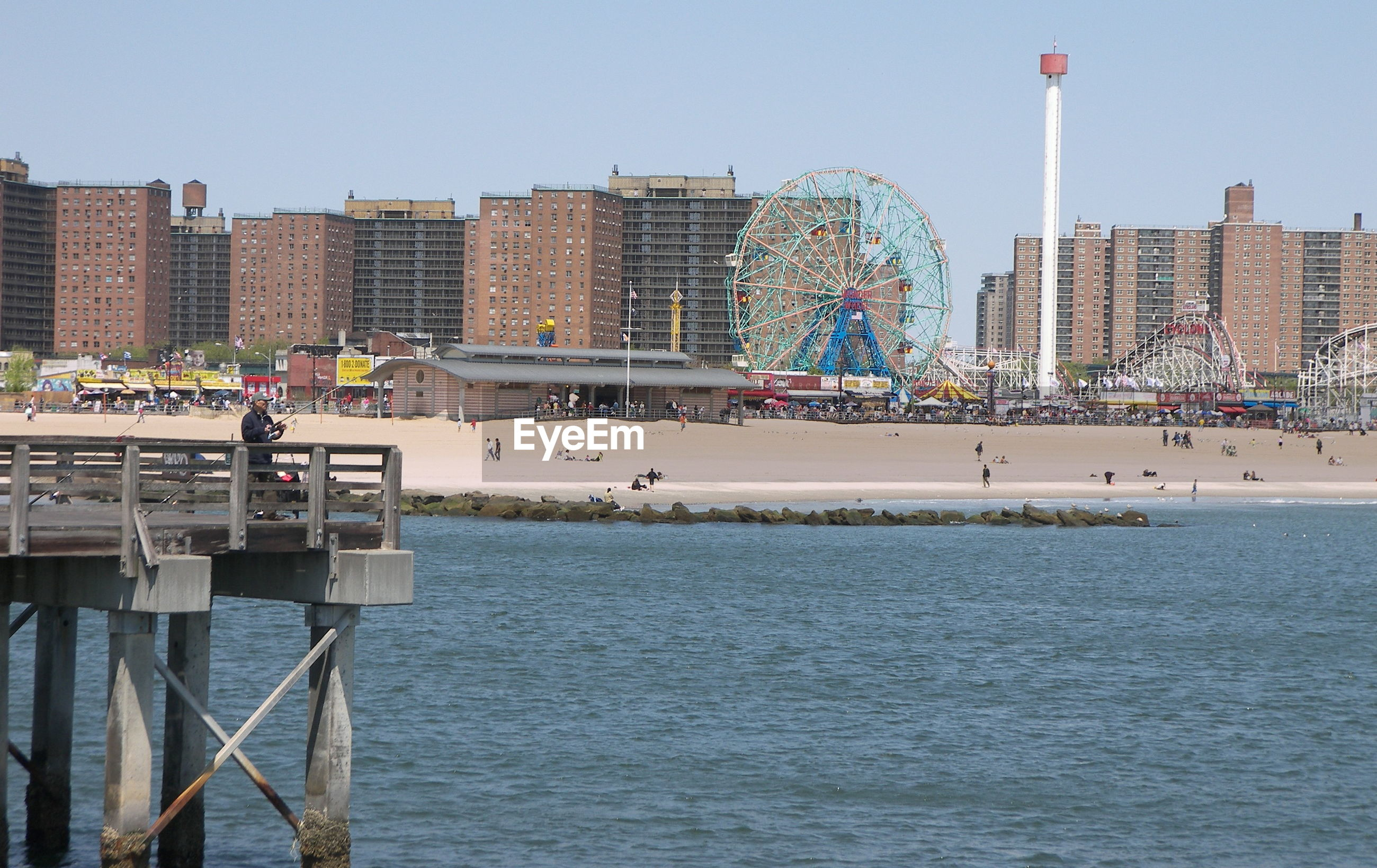 Man fishing on pier against amusement park at coney island