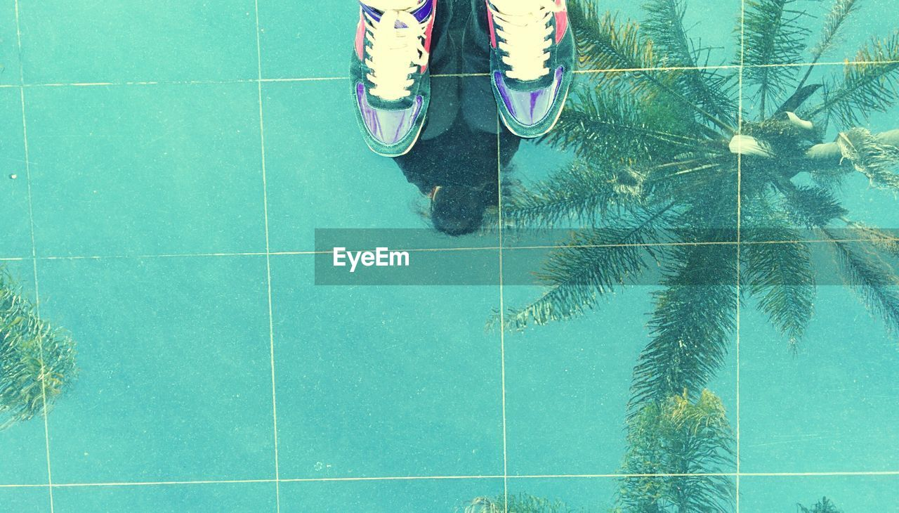 low section, human leg, tile, tiled floor, shoe, green color, day, swimming pool, outdoors, nature, water, people
