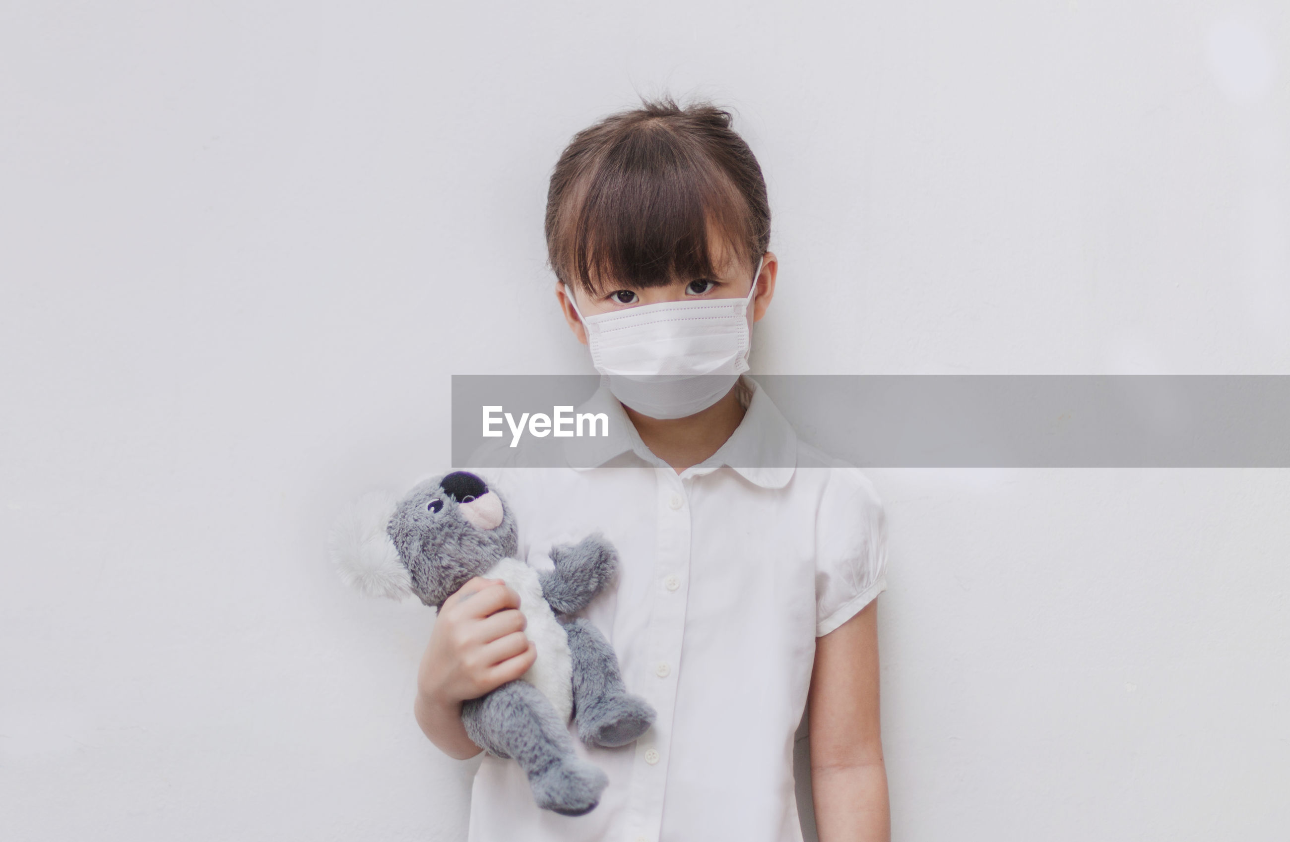 Portrait of girl wearing mask holding stuffed toy against white background