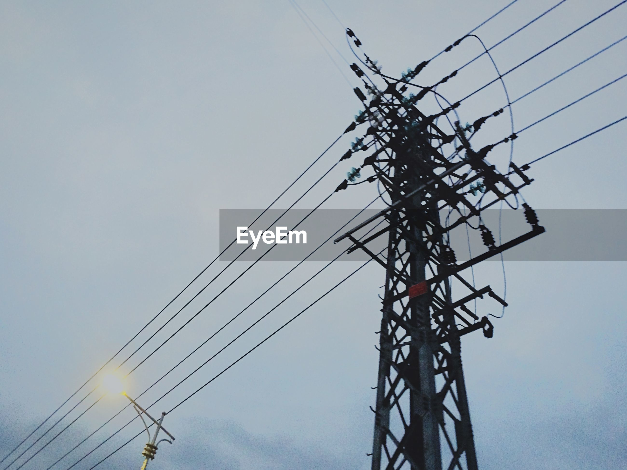 low angle view, power line, electricity, power supply, electricity pylon, fuel and power generation, connection, technology, cable, sky, silhouette, clear sky, outdoors, no people, power cable, blue, tall - high, development, electricity tower, day