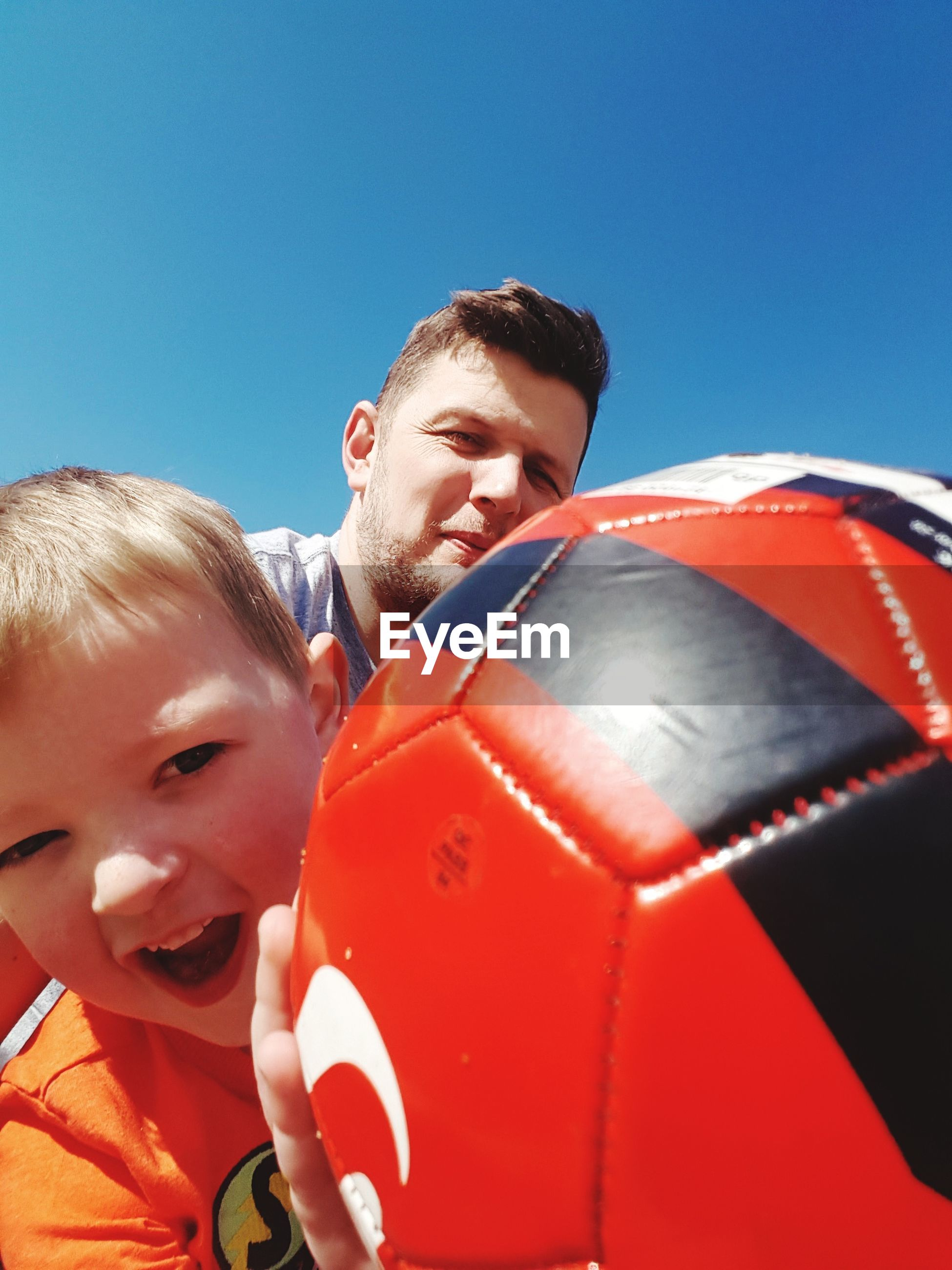 clear sky, boys, real people, leisure activity, two people, sunlight, sunny, young adult, outdoors, sport, lifestyles, playing, day, young men, ball, childhood, low angle view, soccer, togetherness, blond hair, close-up, soccer uniform, sky