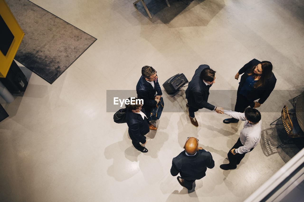 HIGH ANGLE VIEW OF PEOPLE STANDING ON FLOOR IN CORRIDOR