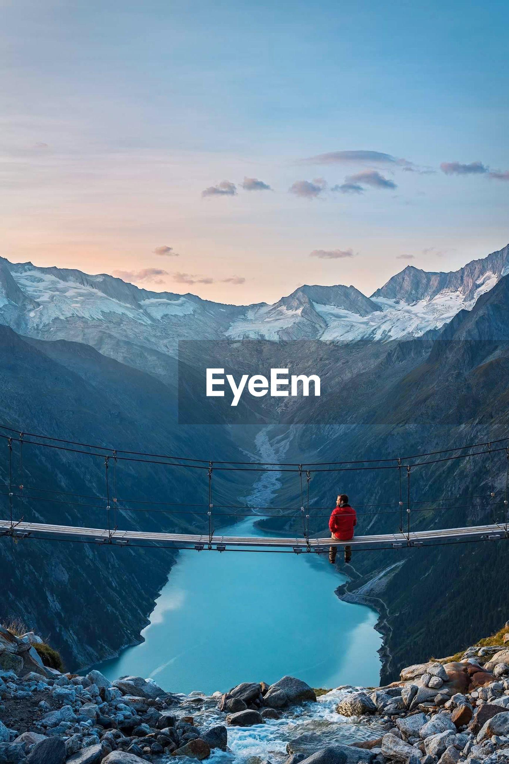 Man sitting on footbridge over lake against mountains