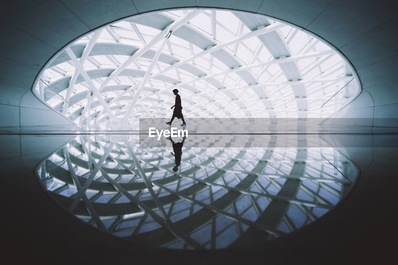 geometric shape, architecture, silhouette, circle, shape, indoors, pattern, built structure, design, real people, glass - material, full length, people, transparent, walking, lifestyles, flooring, sunlight, adult, modern, ceiling