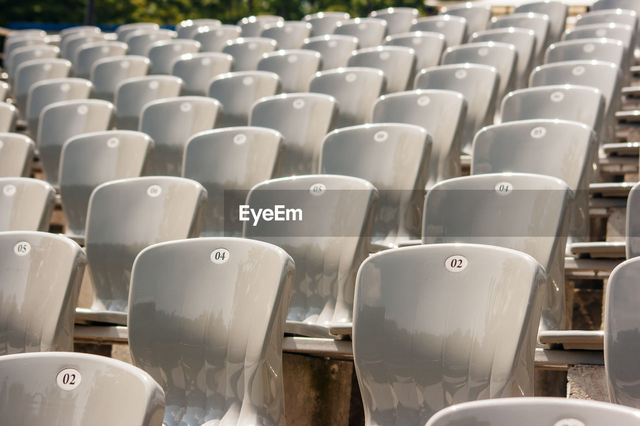 seat, chair, repetition, in a row, side by side, empty, absence, arrangement, no people, stadium, large group of objects, order, abundance, sport, day, bleachers, backgrounds, full frame, sunlight, outdoors