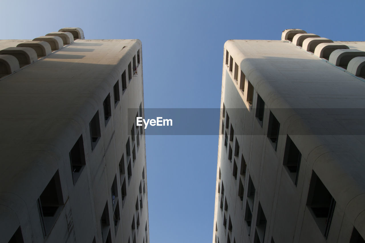 sky, architecture, built structure, clear sky, building exterior, low angle view, nature, no people, building, city, day, blue, outdoors, sunlight, residential district, modern, office building exterior, copy space, window, wall - building feature, skyscraper, directly below