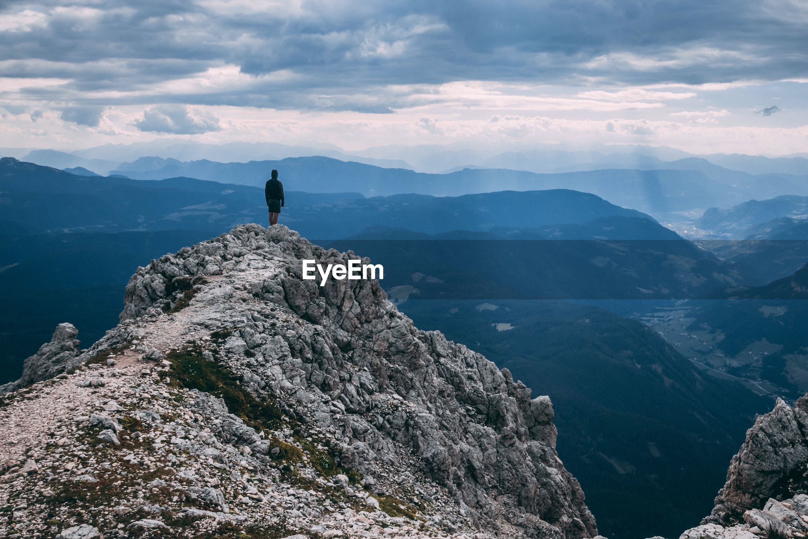 Rear view of man looking at landscape while standing on mountain against cloudy sky