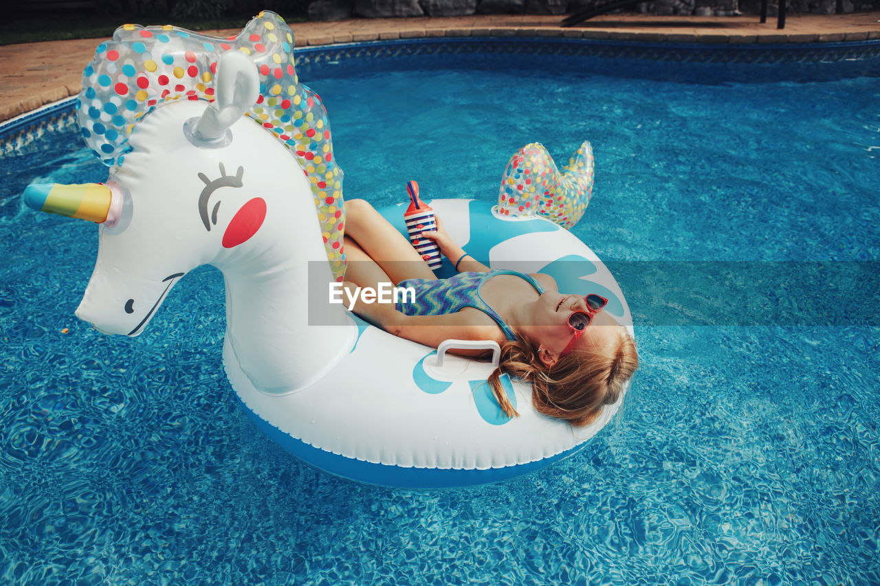 Cute adorable girl in sunglasses with drink lying on inflatable ring unicorn. kid child enjoying