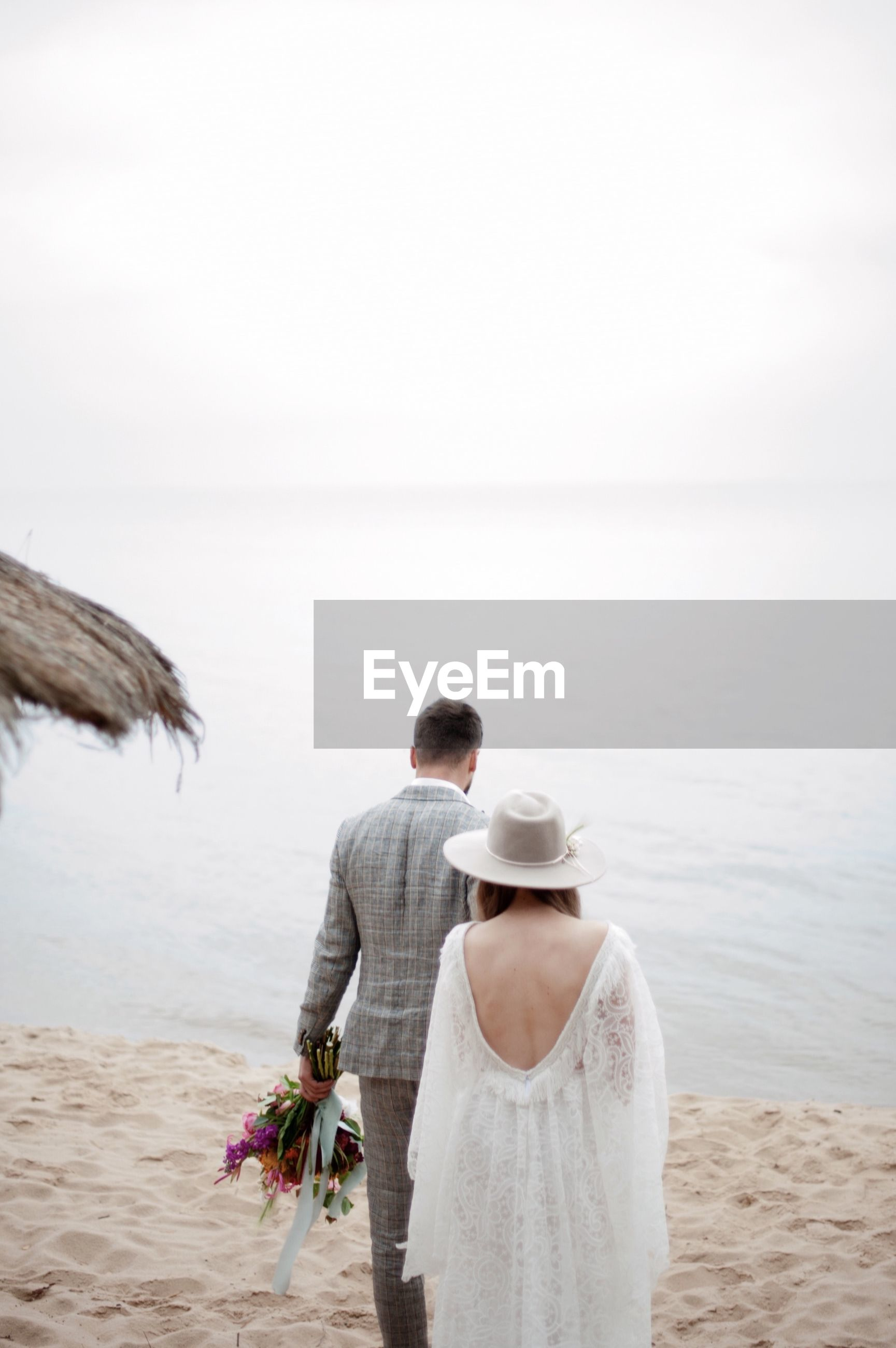 Rear view of romantic newlywed couple walking at beach against sky