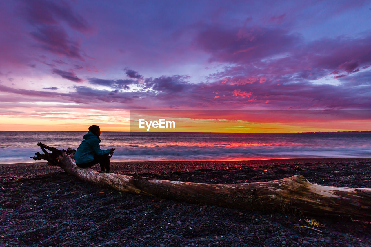 sunset, sky, sea, beauty in nature, scenics, nature, water, sitting, orange color, real people, full length, tranquil scene, cloud - sky, outdoors, tranquility, beach, horizon over water, leisure activity, lifestyles, men, day, people