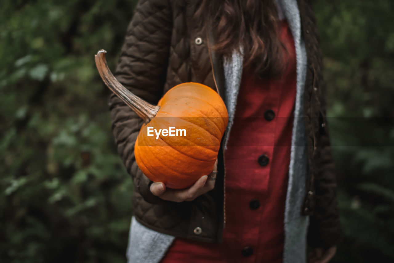 Midsection of woman holding pumpkin while standing against plants