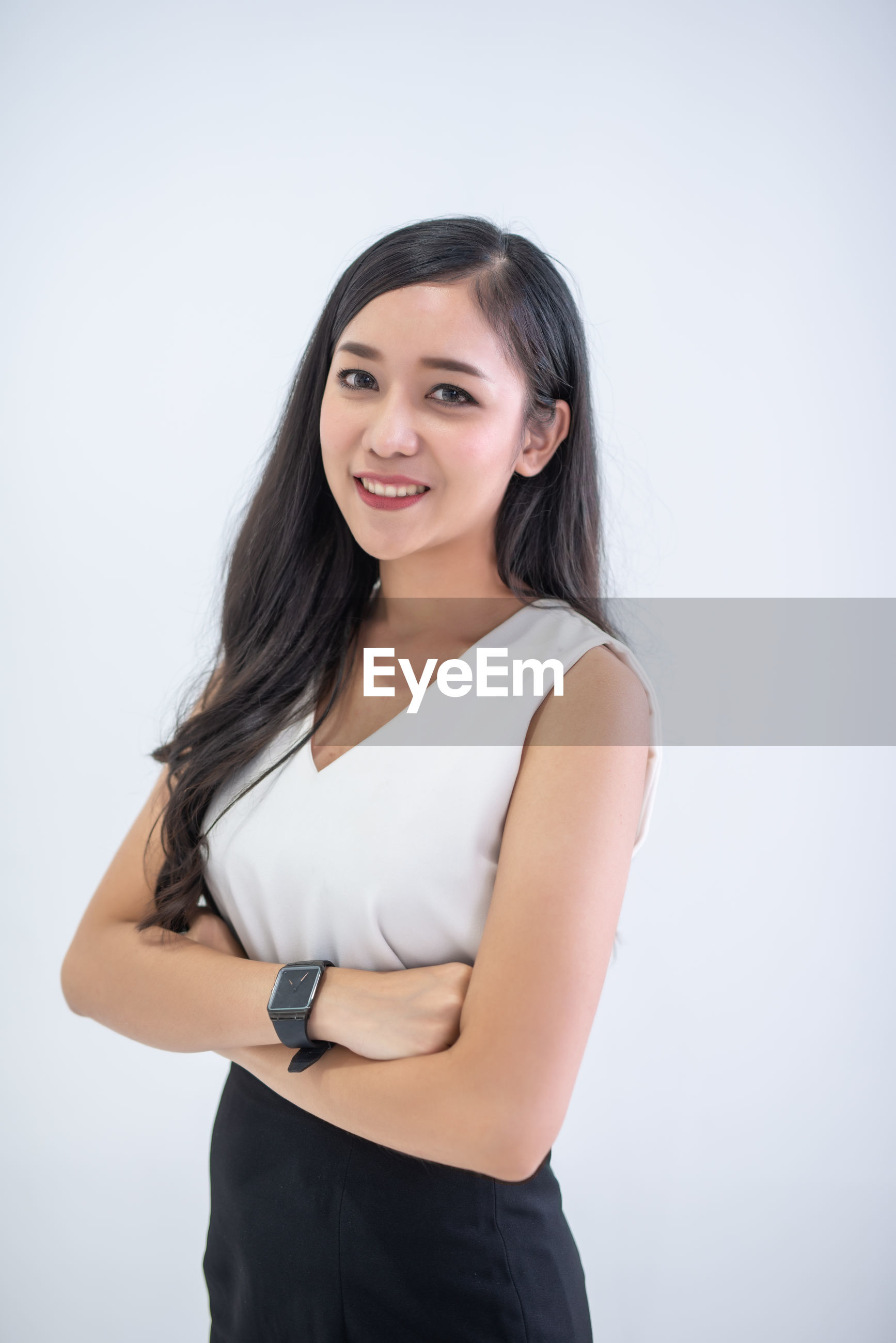 Portrait of confident businesswoman with arms crossed standing against white background