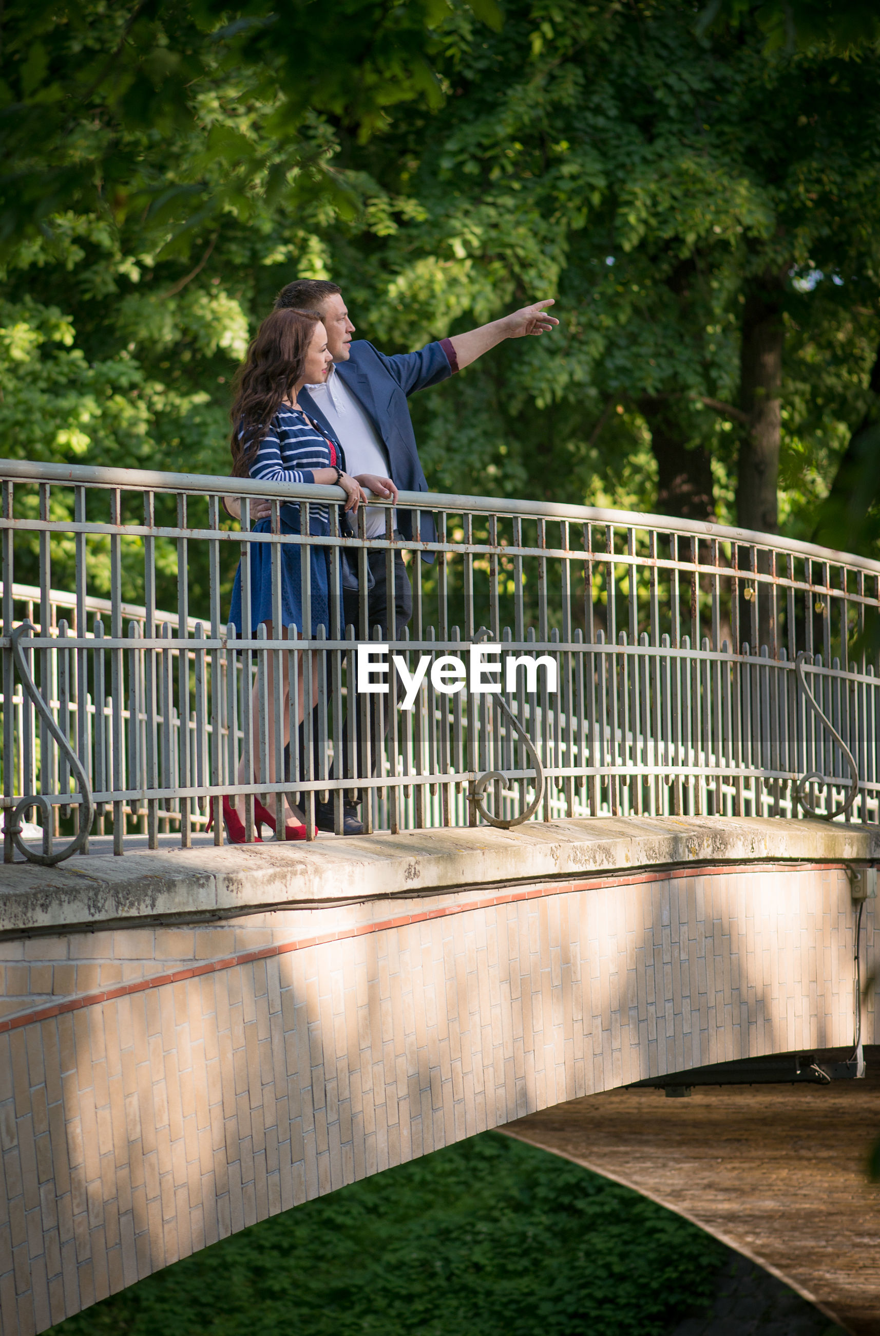 Low angle view of man showing something to woman while standing on footbridge at public park