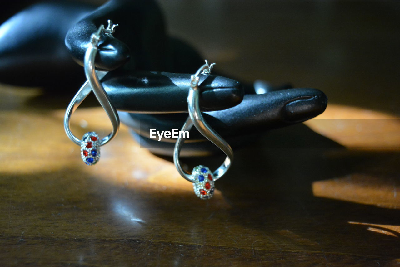 Close-up of earrings on table