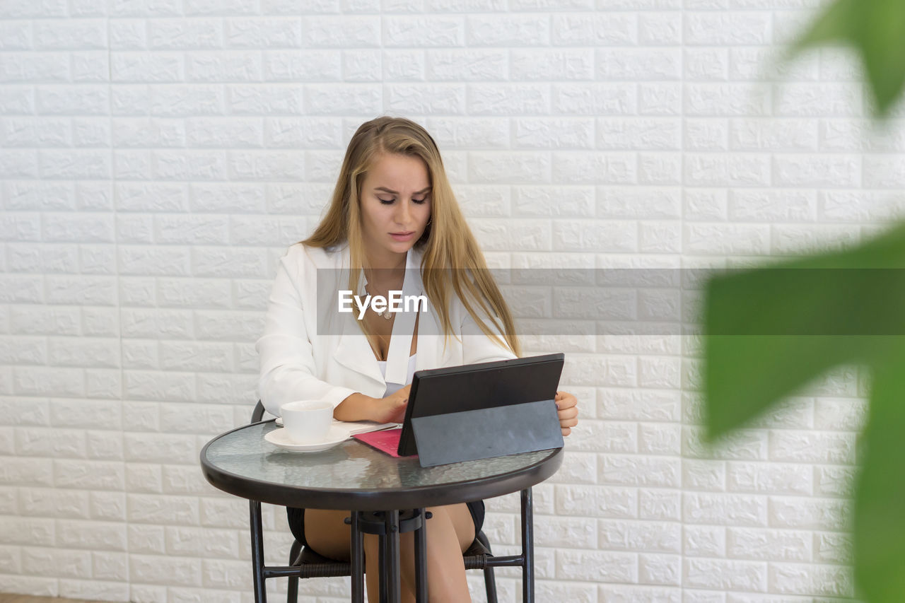 Young Businesswoman Using Digital Tablet While Sitting At Table In Office