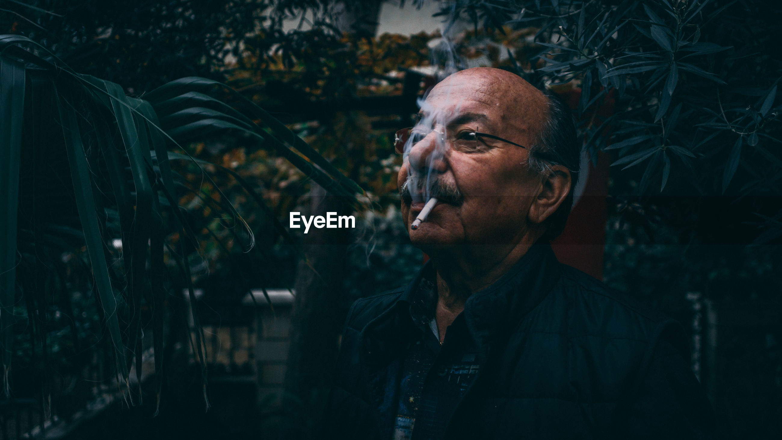 Man smoking cigarette against trees