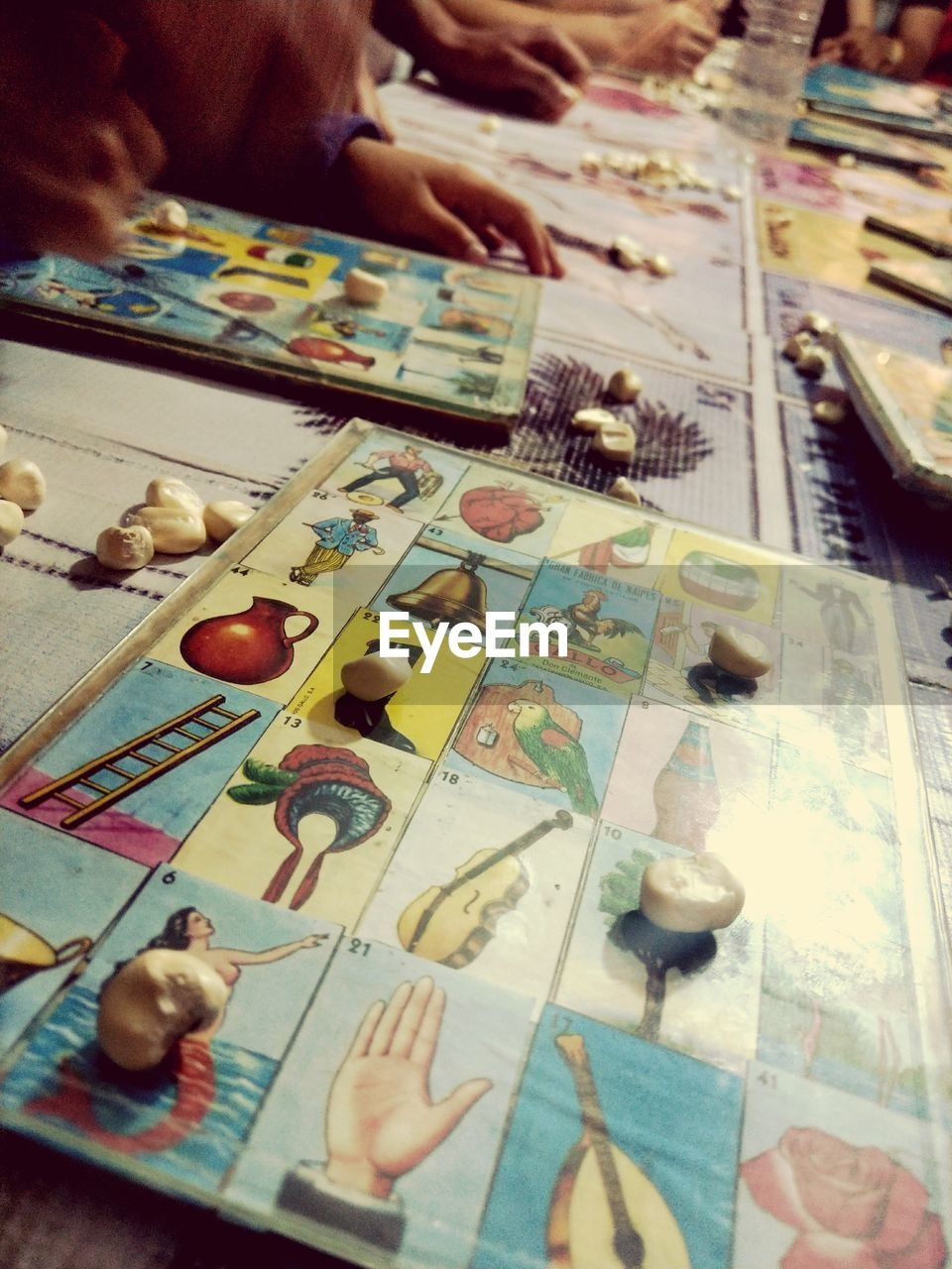 selective focus, indoors, human hand, real people, human body part, table, close-up, choice, leisure games, one person, day, people