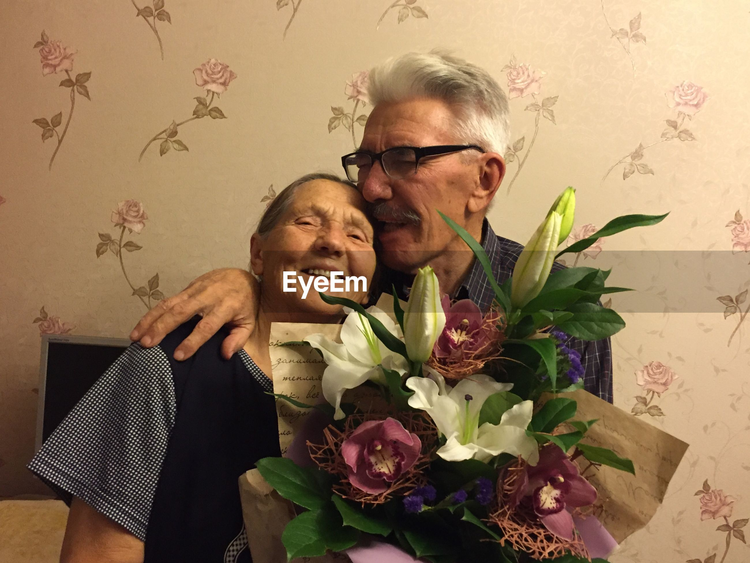 Portrait of smiling senior couple kissing at home