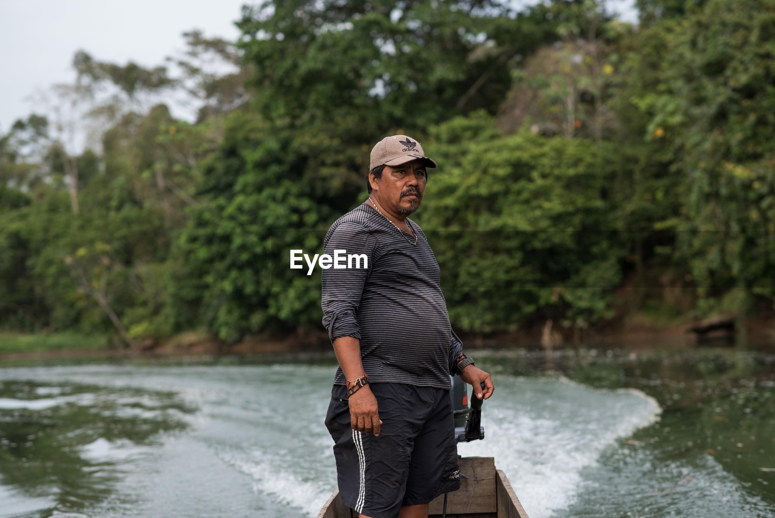 FULL LENGTH OF MAN STANDING AGAINST RIVER