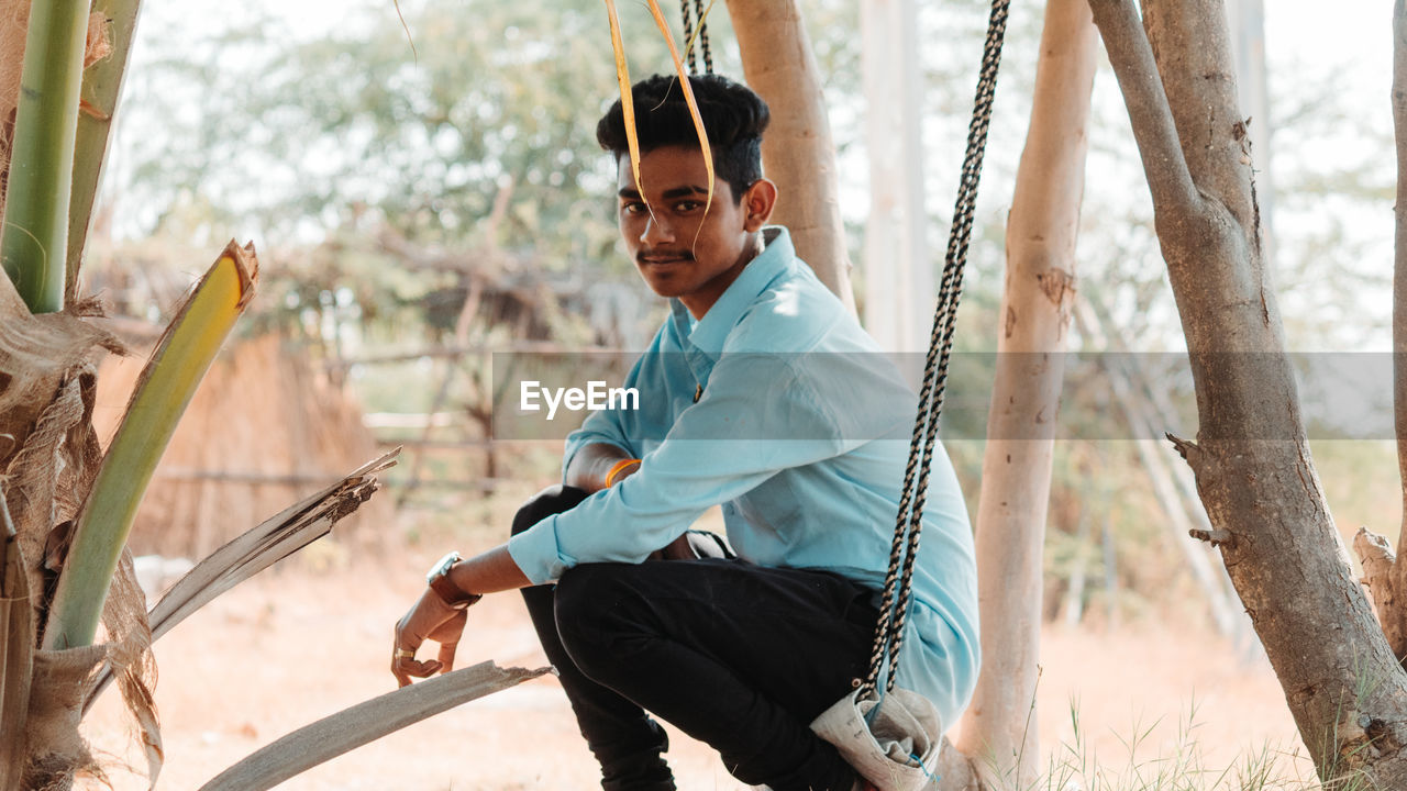 young men, one person, real people, young adult, tree, casual clothing, lifestyles, day, leisure activity, sitting, focus on foreground, looking at camera, swing, plant, land, nature, males, outdoors