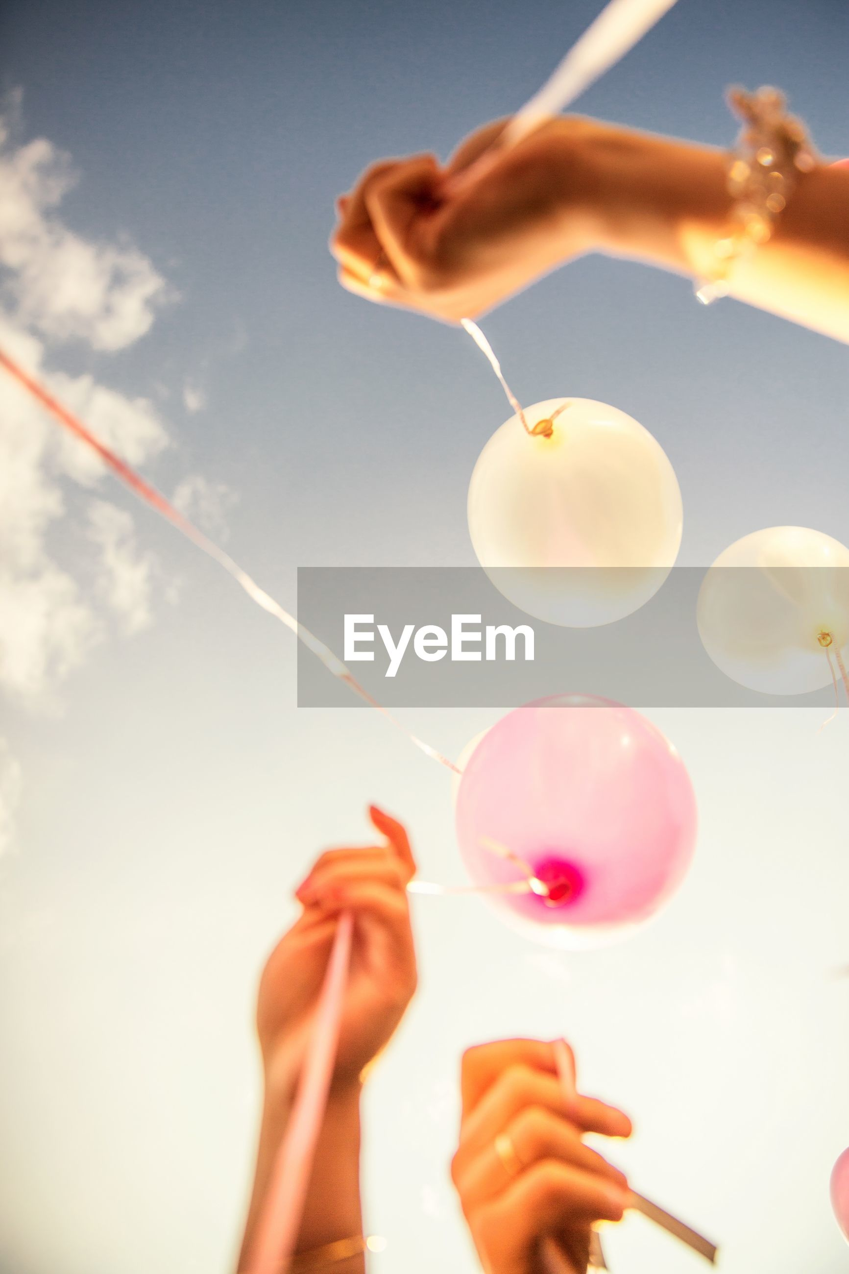 Low angle view of hands holding helium balloons against sky