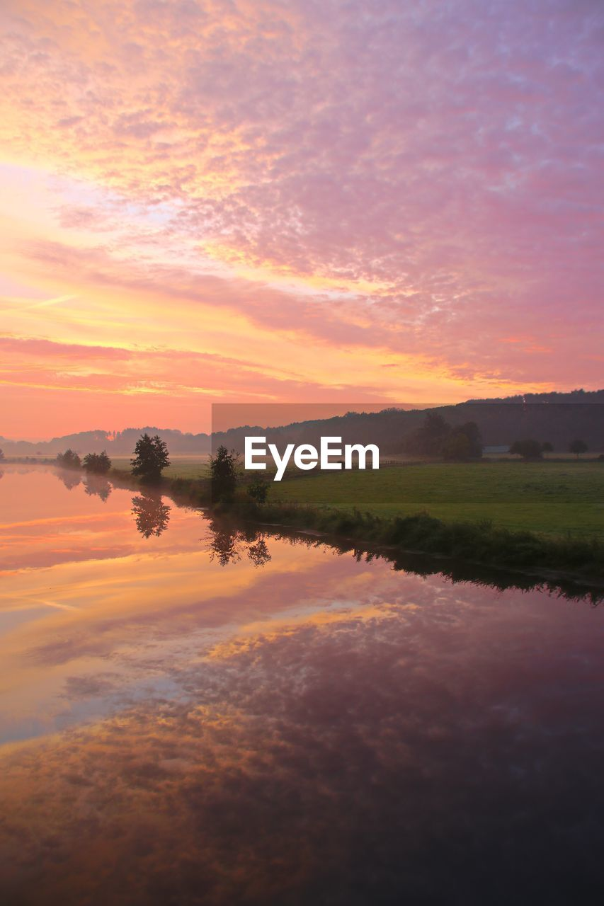 sky, sunset, beauty in nature, scenics - nature, tranquil scene, tranquility, water, cloud - sky, orange color, idyllic, reflection, no people, non-urban scene, nature, lake, waterfront, environment, plant, landscape, outdoors