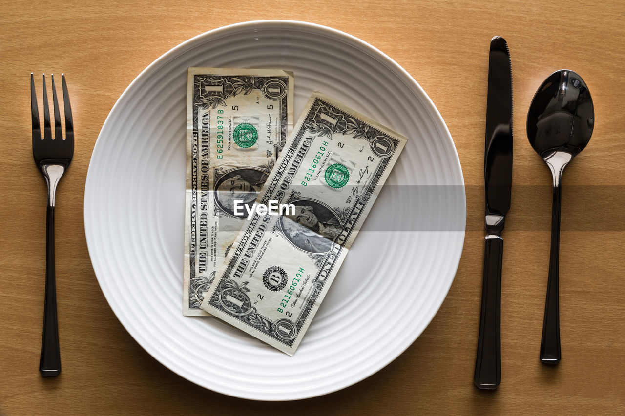 Close-Up Of Paper Currencies In Plate On Table