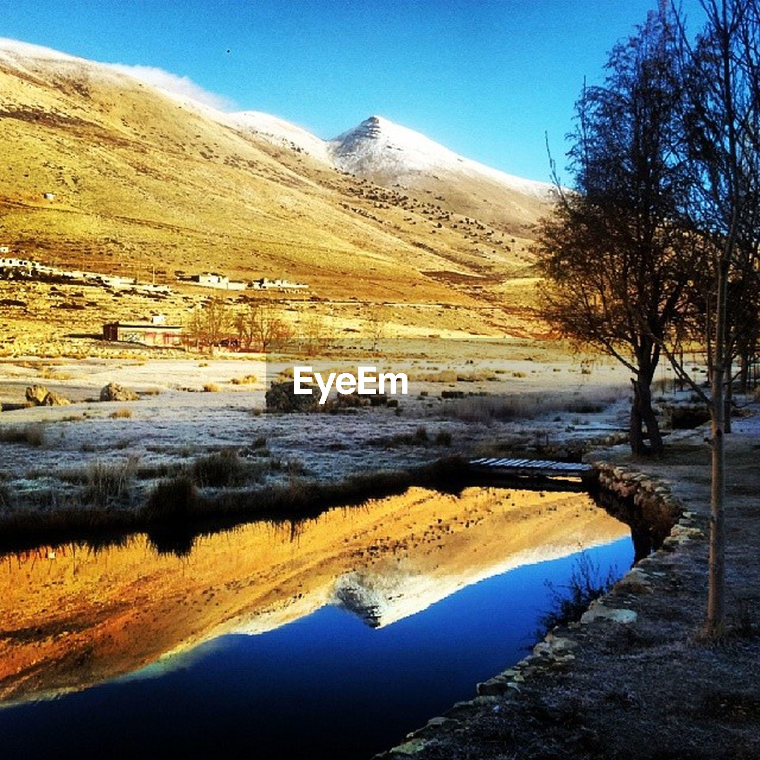 mountain, water, tranquil scene, tranquility, scenics, beauty in nature, blue, lake, clear sky, landscape, mountain range, nature, tree, reflection, river, non-urban scene, idyllic, sky, bare tree, sunlight