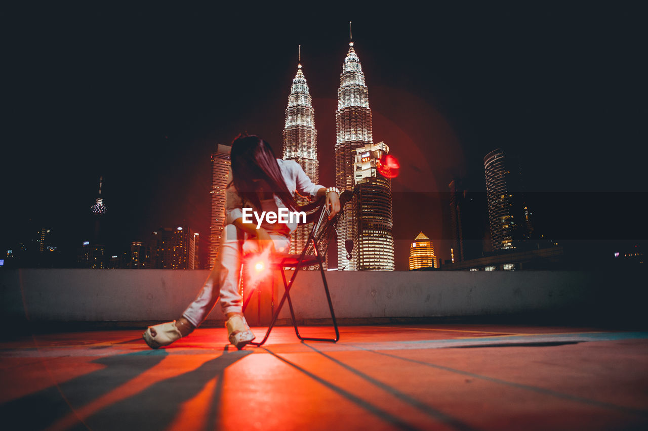 Low angle view of woman sitting on chair against illuminated building in city at night
