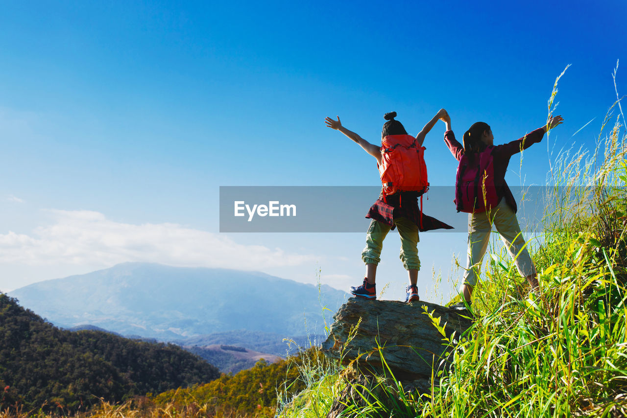 Hikers standing on rock against blue sky