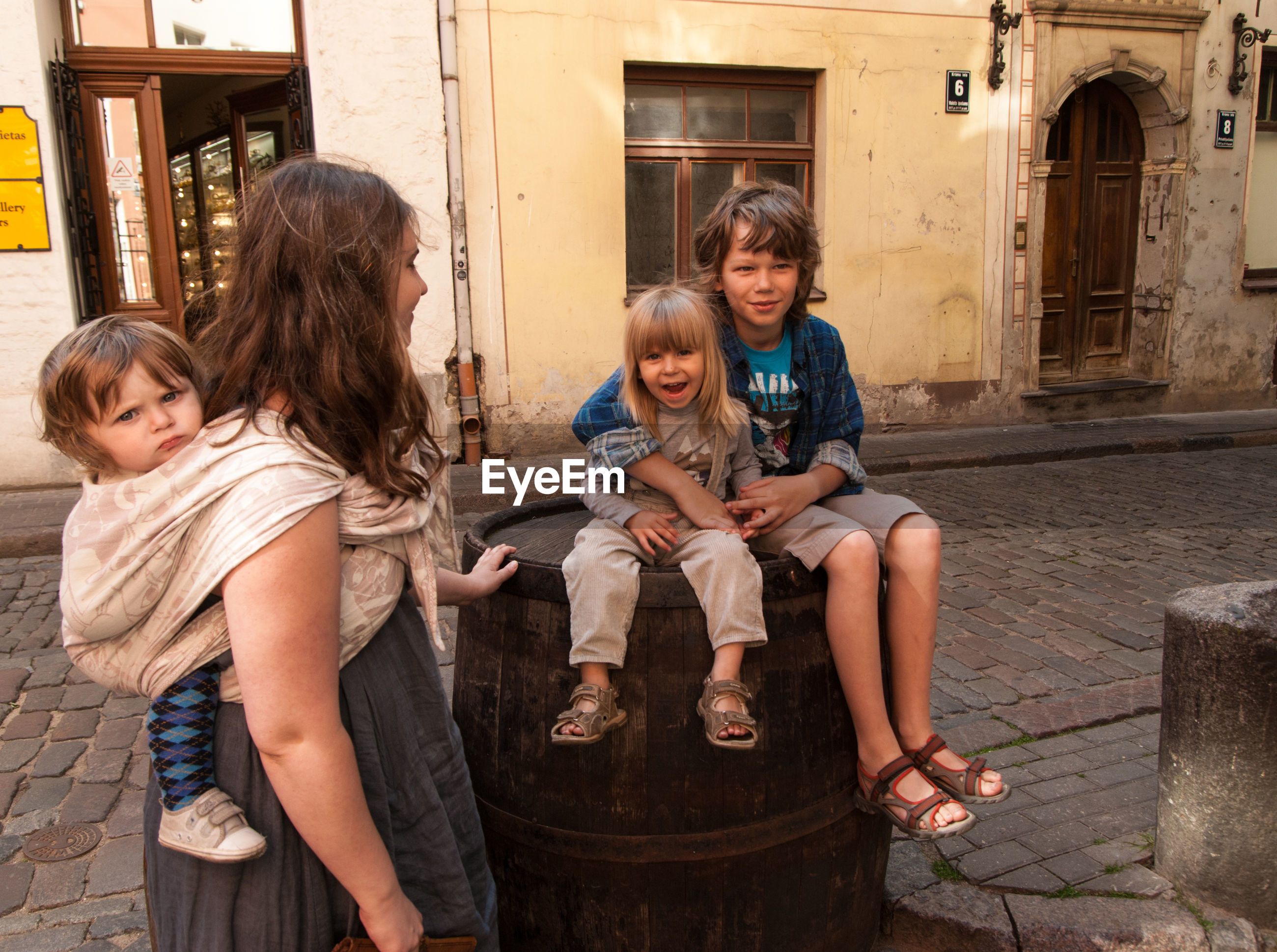 Woman with children sitting on barrel against old building in town
