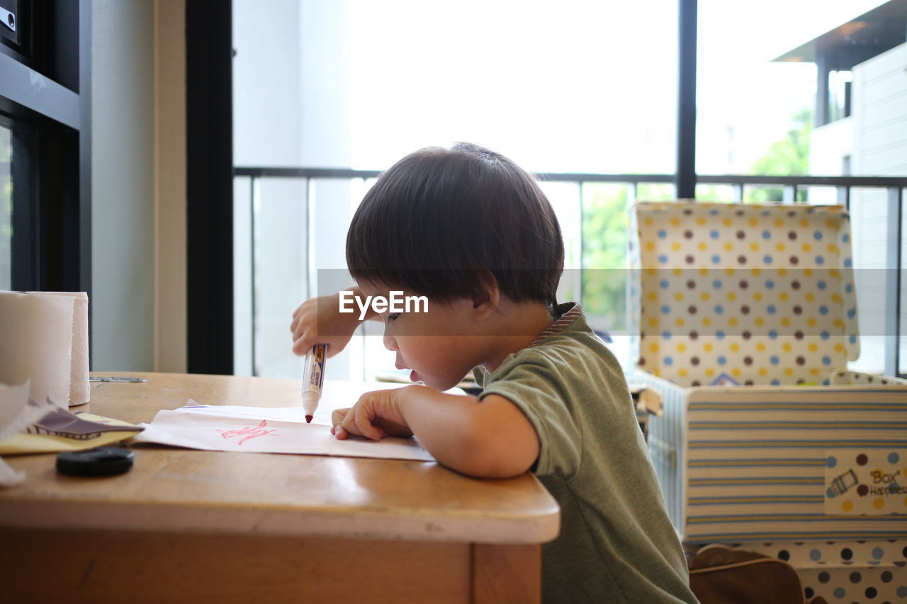 Boy Sitting By Table At Home
