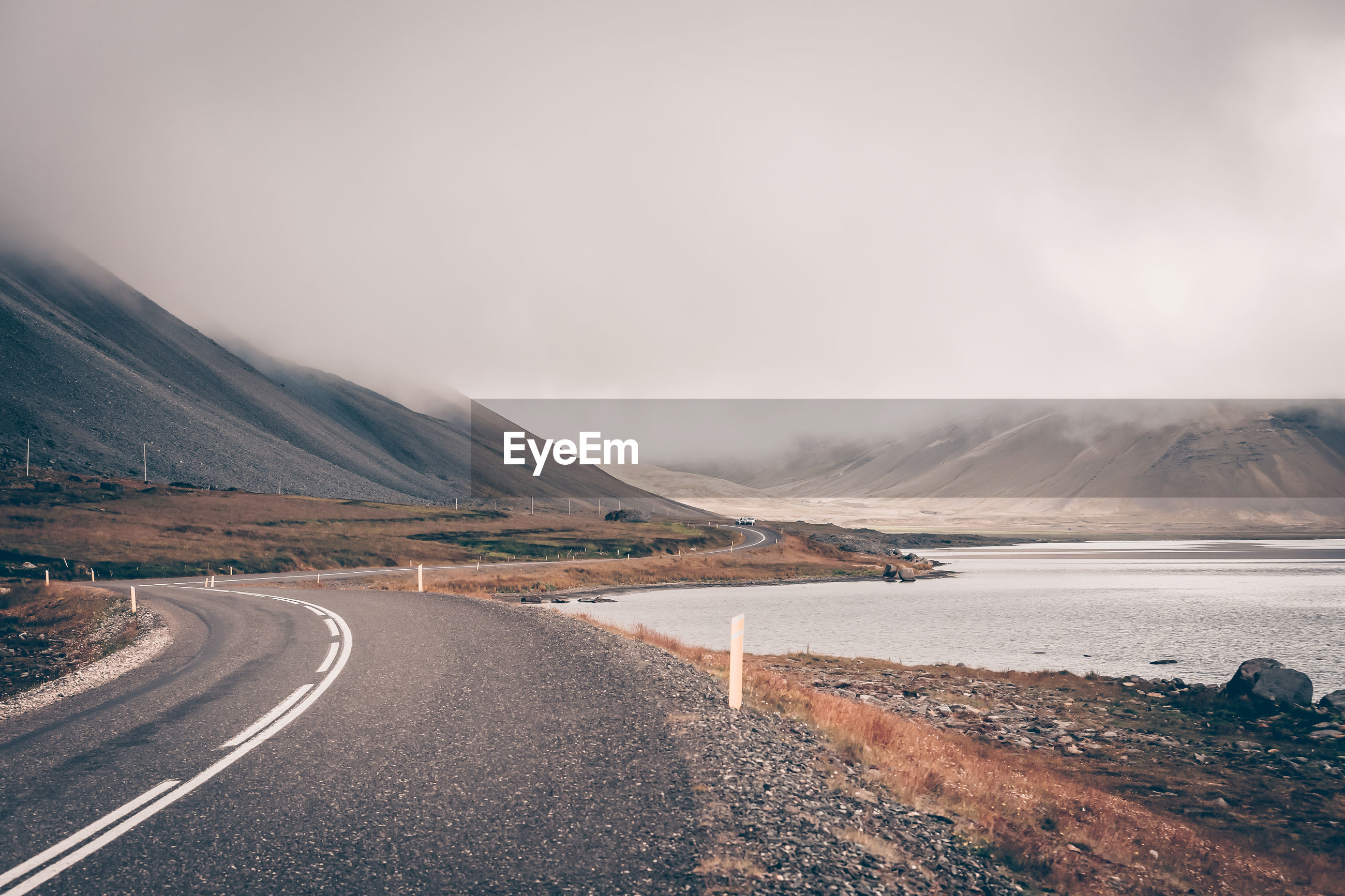Road by lake against sky