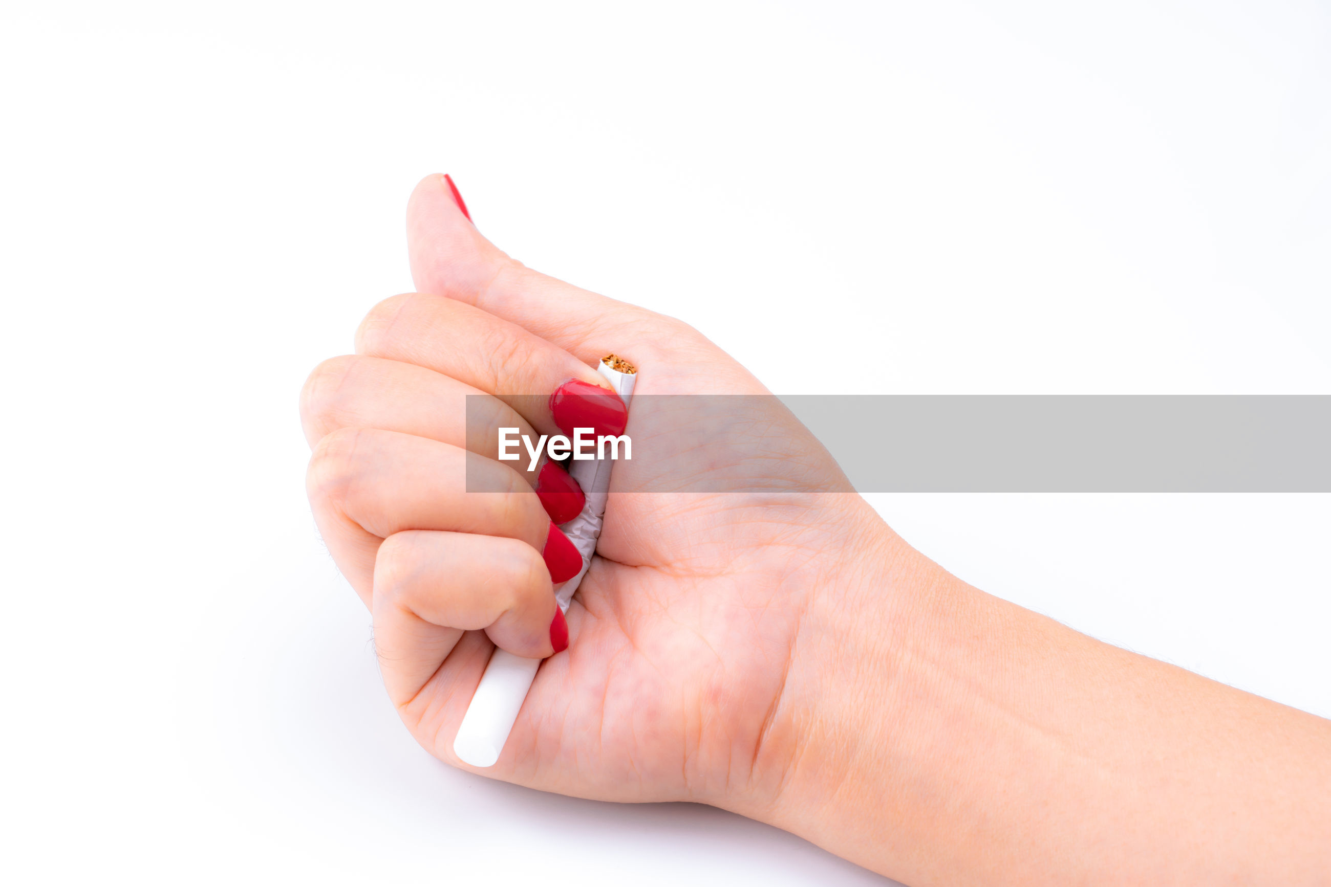 Close-up of hand breaking cigarette over white background