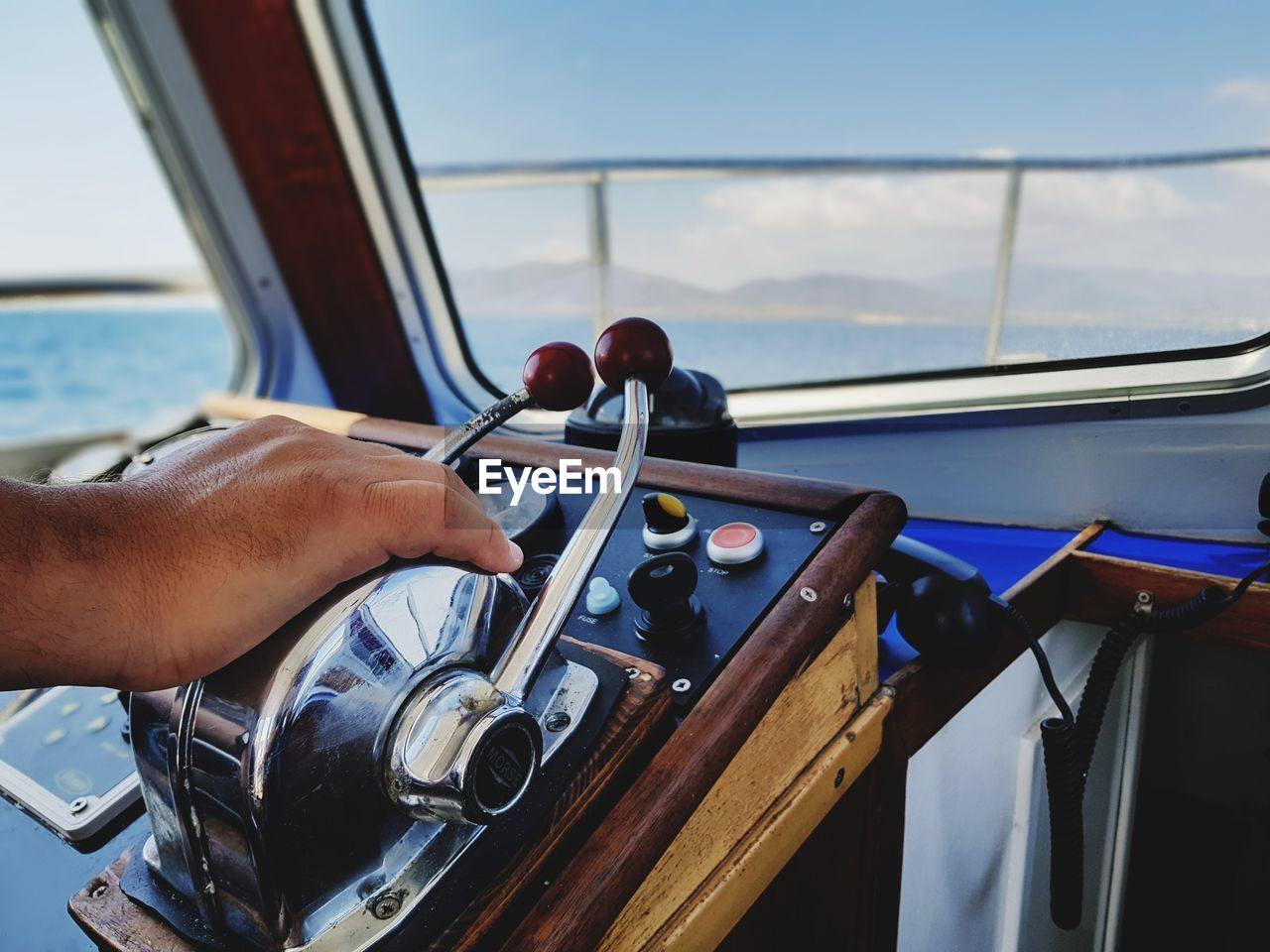 Cropped Hand Of Man On Control Panel In Recreational Boat