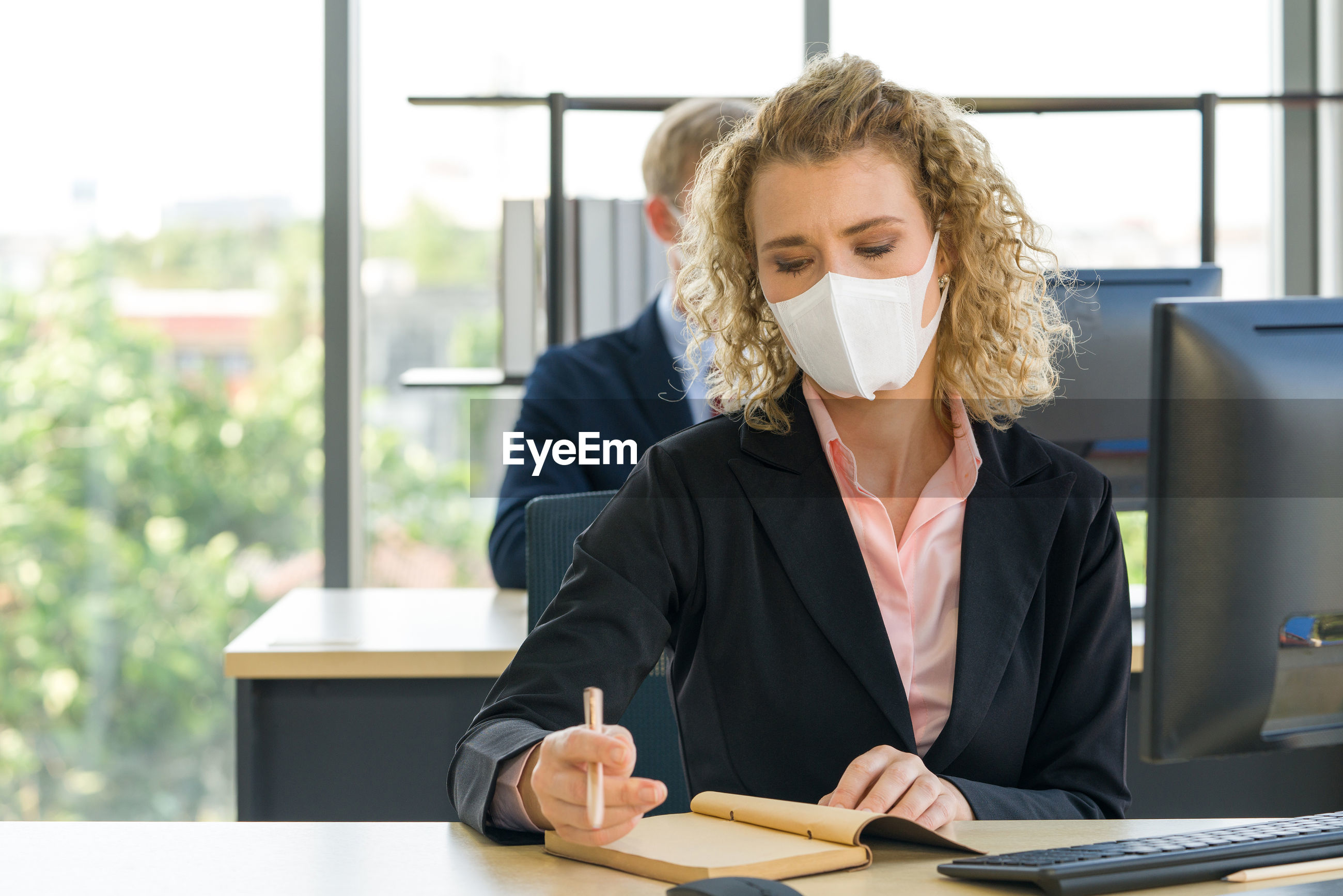 Businesswoman wearing mask reading book on desk in office