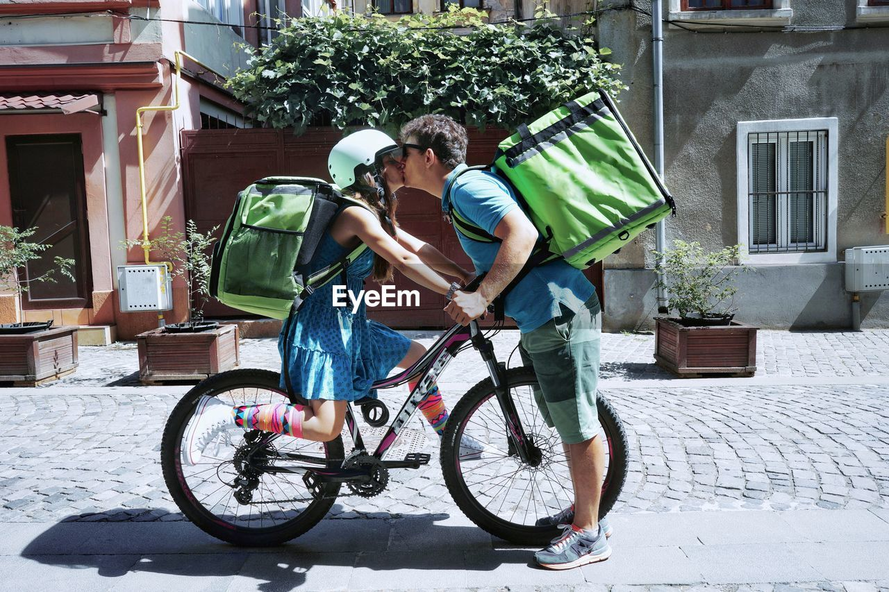 Couple With Bicycle Kissing On Street In City