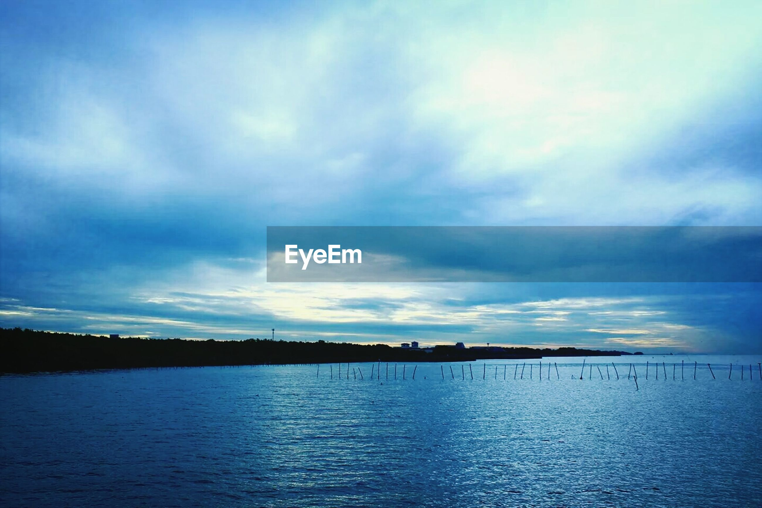 water, sky, tranquil scene, tranquility, waterfront, scenics, cloud - sky, beauty in nature, sea, nature, cloud, cloudy, idyllic, lake, reflection, blue, dusk, calm, silhouette, outdoors