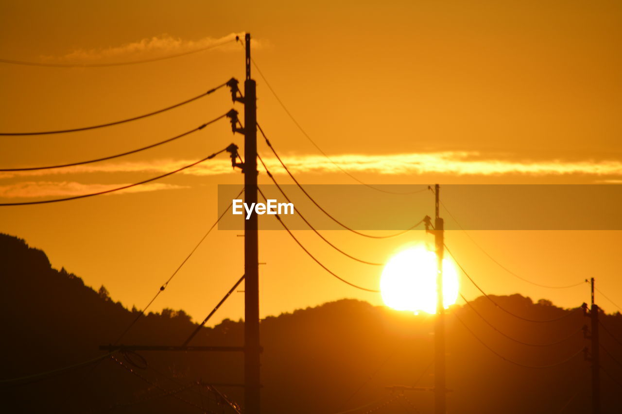 sky, sunset, electricity, silhouette, connection, sun, orange color, cable, technology, electricity pylon, beauty in nature, nature, power supply, no people, fuel and power generation, power line, cloud - sky, sunlight, outdoors, low angle view, lens flare, telephone line, complexity, brightly lit, romantic sky, electrical equipment