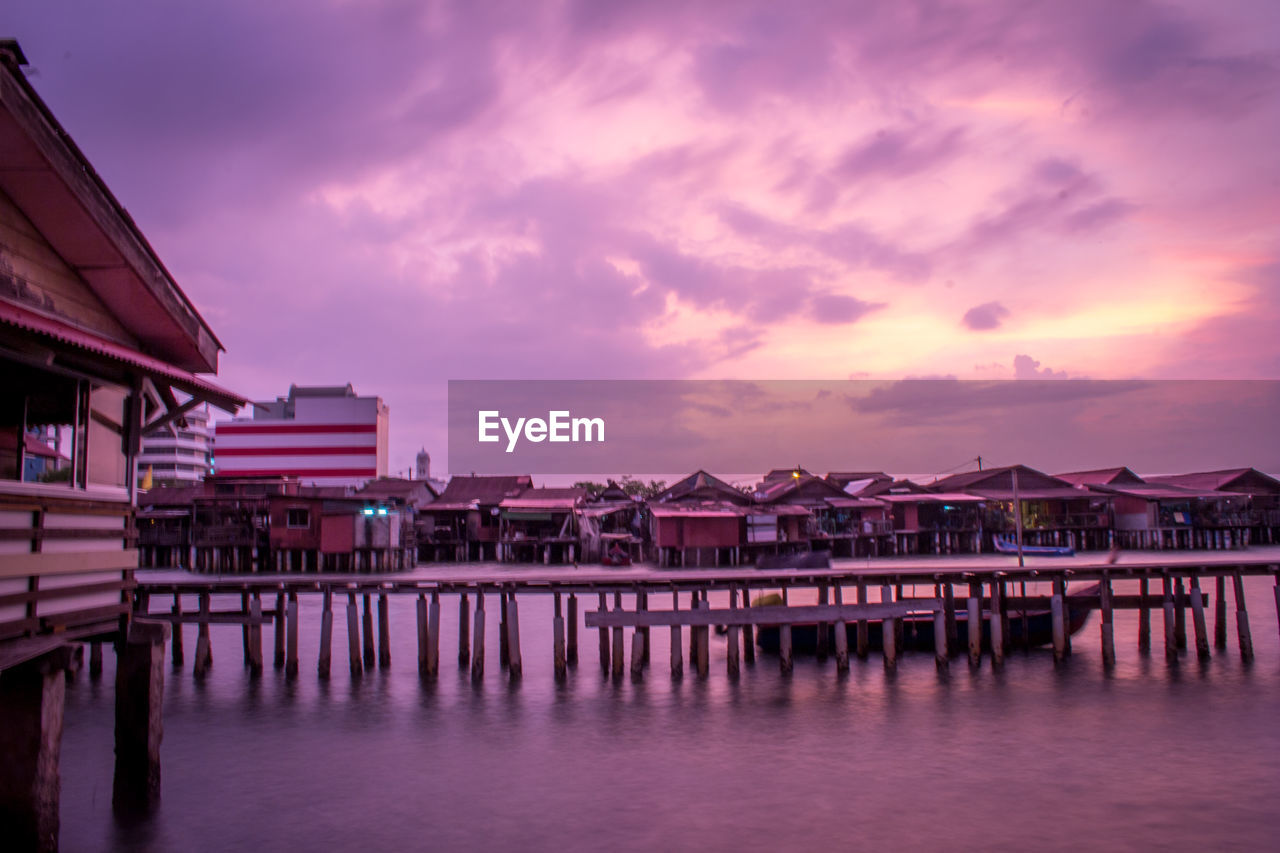 architecture, building exterior, built structure, sky, water, sunset, house, building, cloud - sky, residential district, dusk, waterfront, nature, beauty in nature, stilt house, reflection, scenics - nature, no people, tranquil scene, outdoors, purple, bay