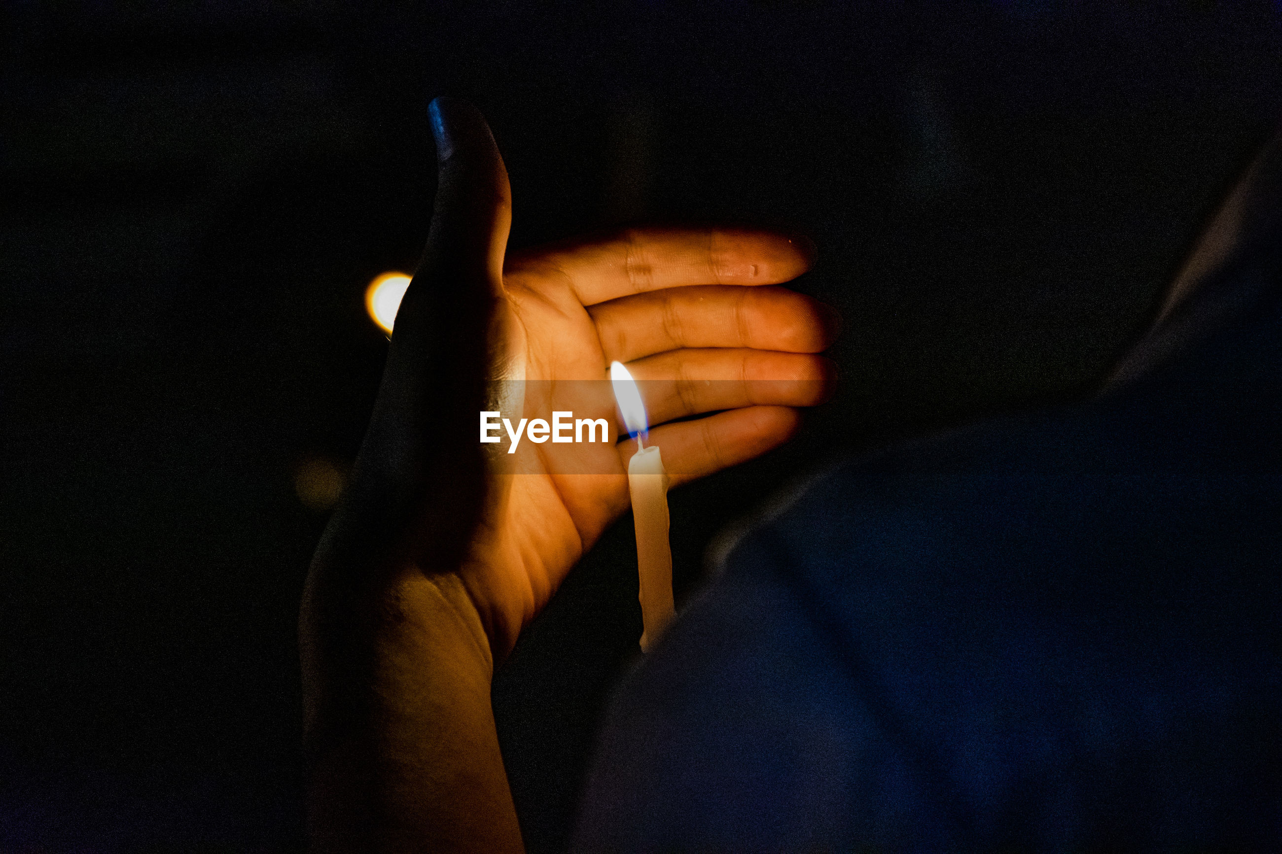 Close-up of person holding candle in darkroom