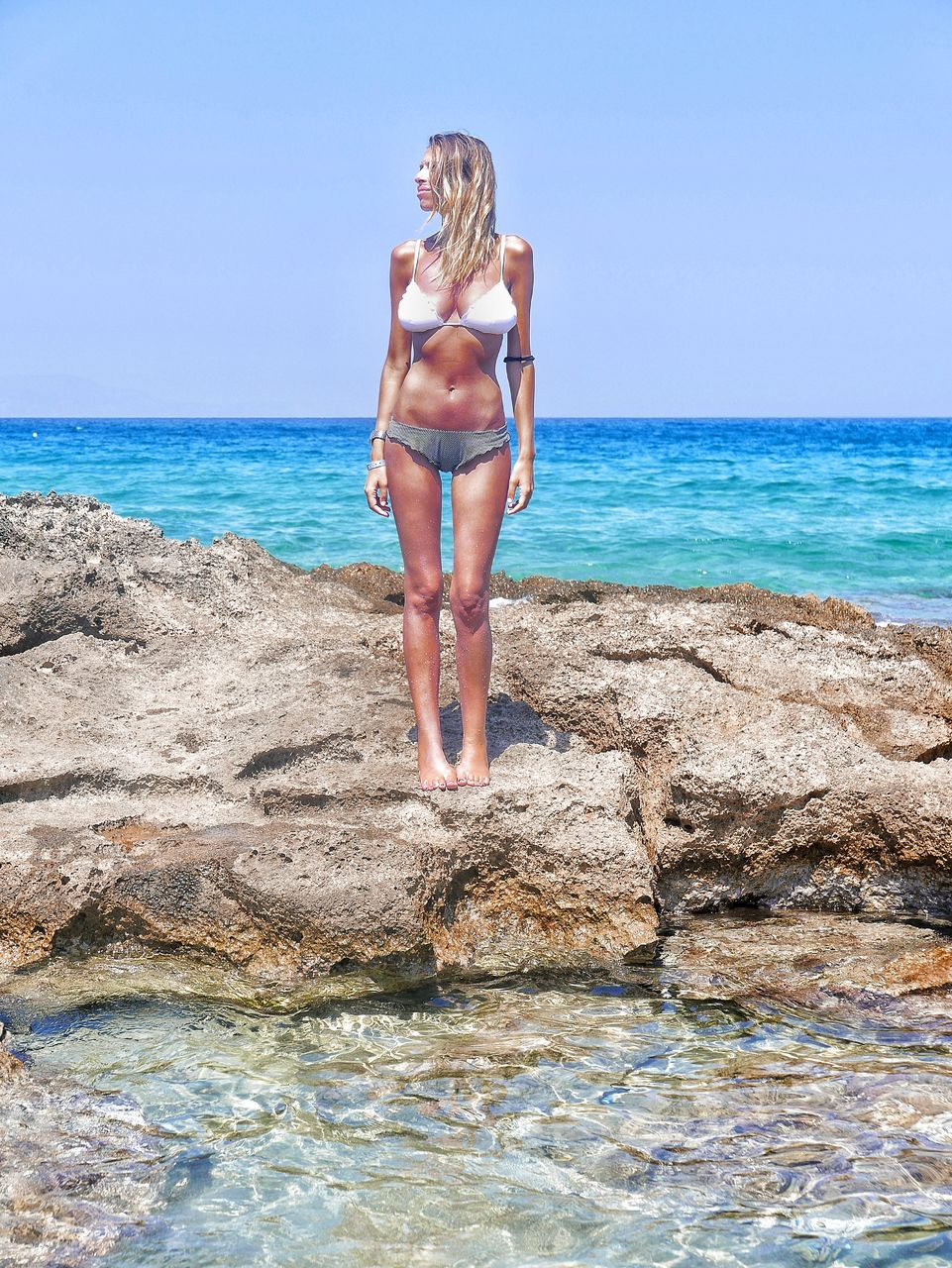 sea, young adult, young women, bikini, real people, one person, leisure activity, water, full length, standing, lifestyles, beach, rear view, nature, horizon over water, day, beautiful woman, outdoors, beauty in nature, clear sky, vacations, sky, scenics, ankle deep in water, blond hair, people